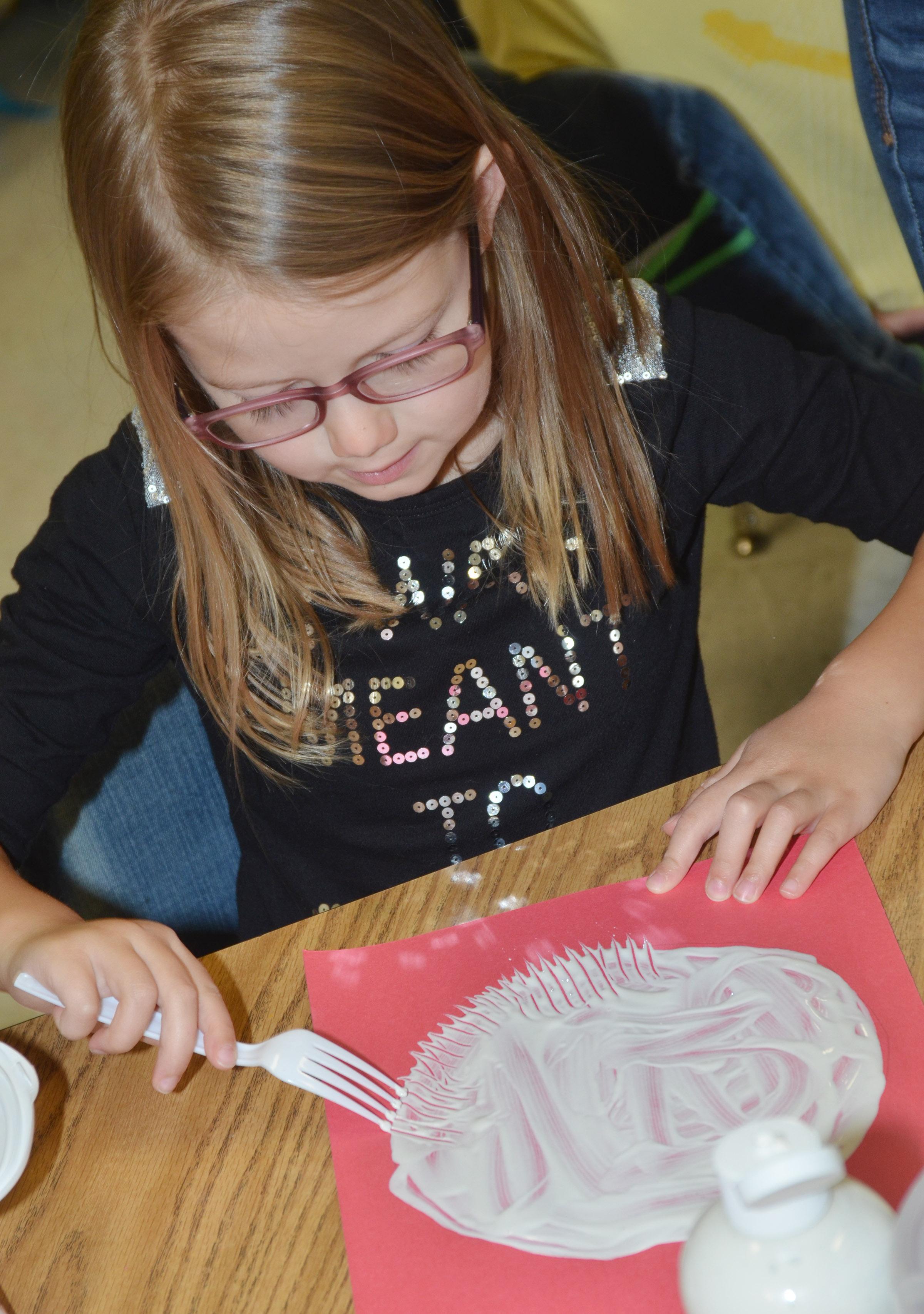 CES kindergartener Emmaline Vespie paints with a fork to make her panda's face.