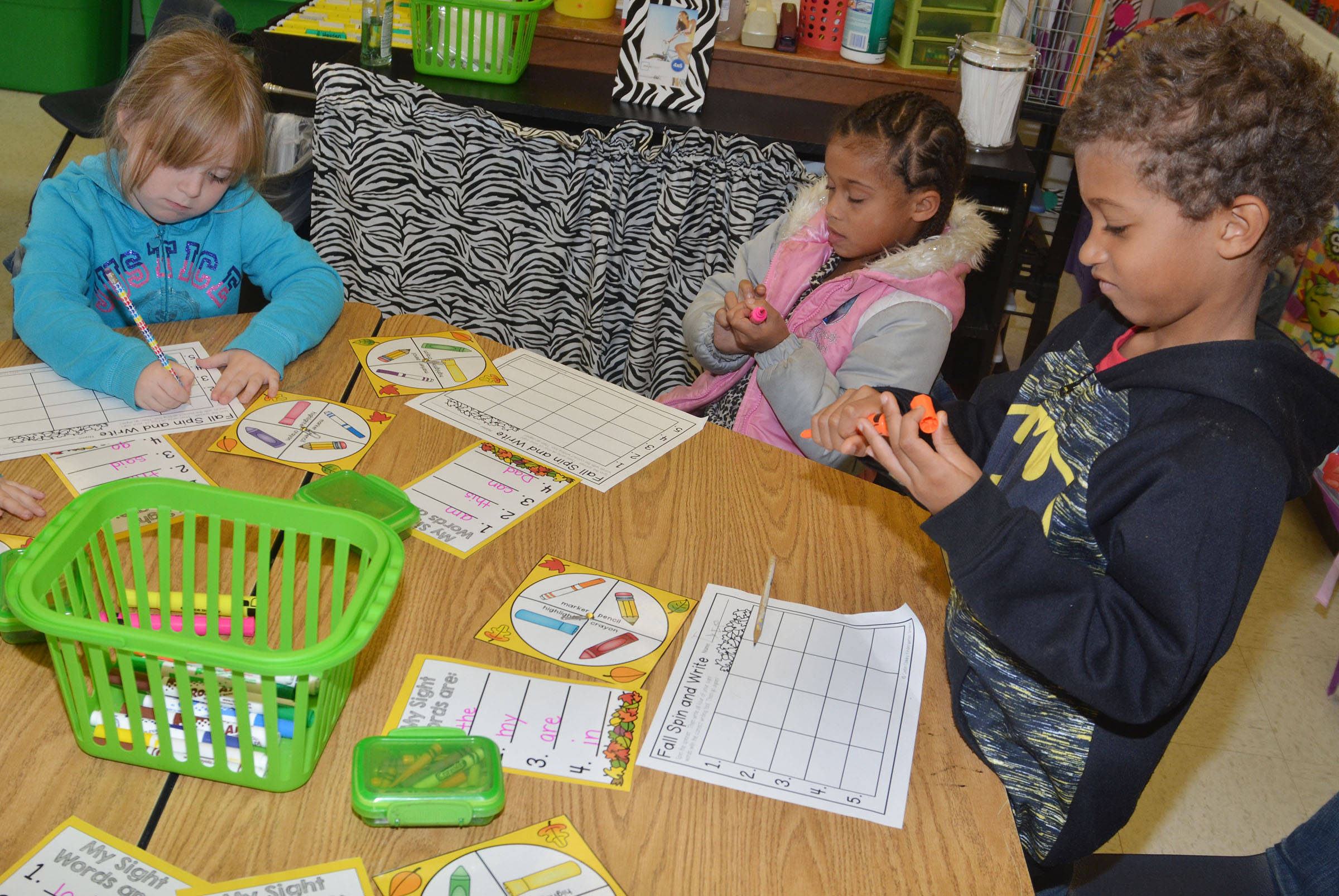 CES kindergarteners, from left, Briley Sapp, Jyra Welch and Tyce Owens use pencils and highlighters to write their sight words.