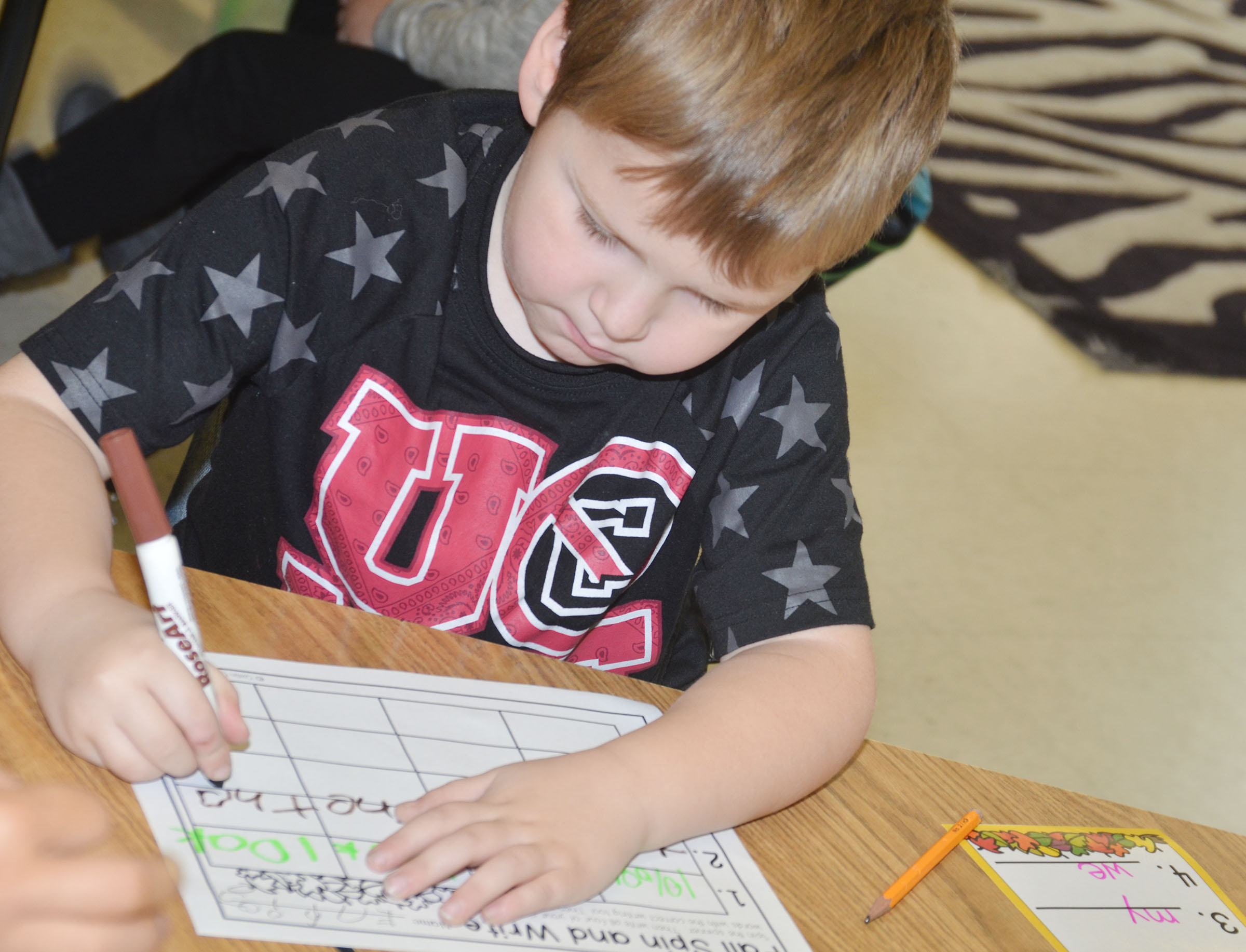 CES kindergartener Enrique McDonald uses a marker to write his sight words.