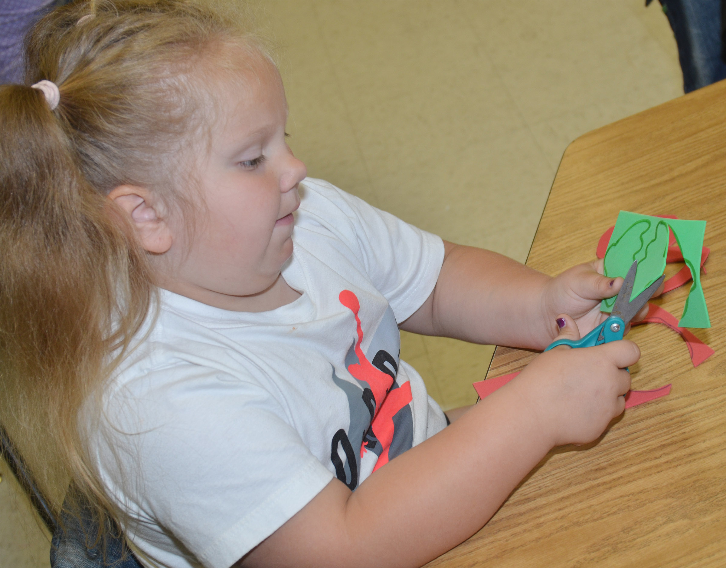 CES kindergartener ReAnna Jeffries cuts out her strawberry glasses.