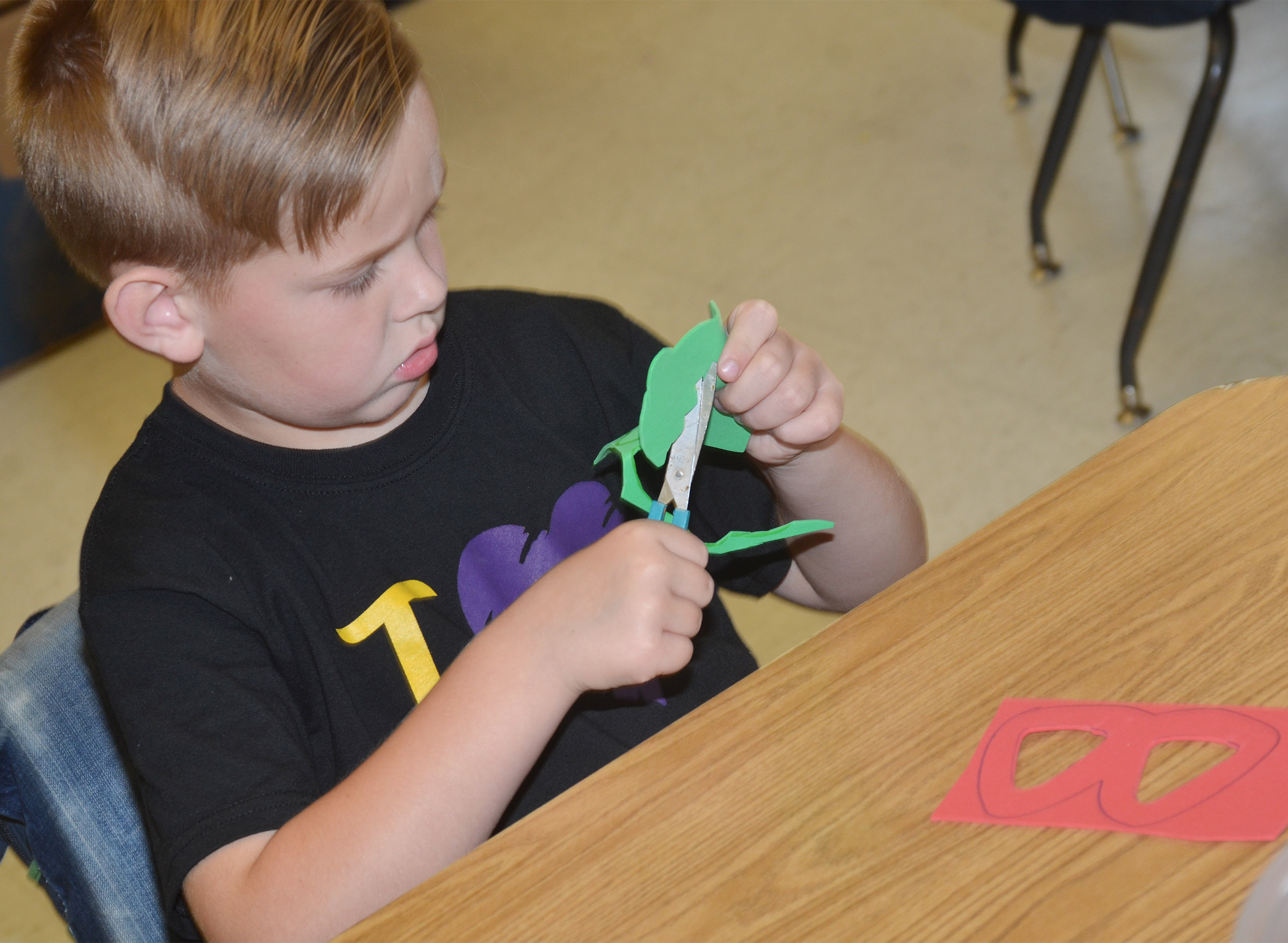 CES kindergartener John Hagan Newton cuts out his strawberry glasses.