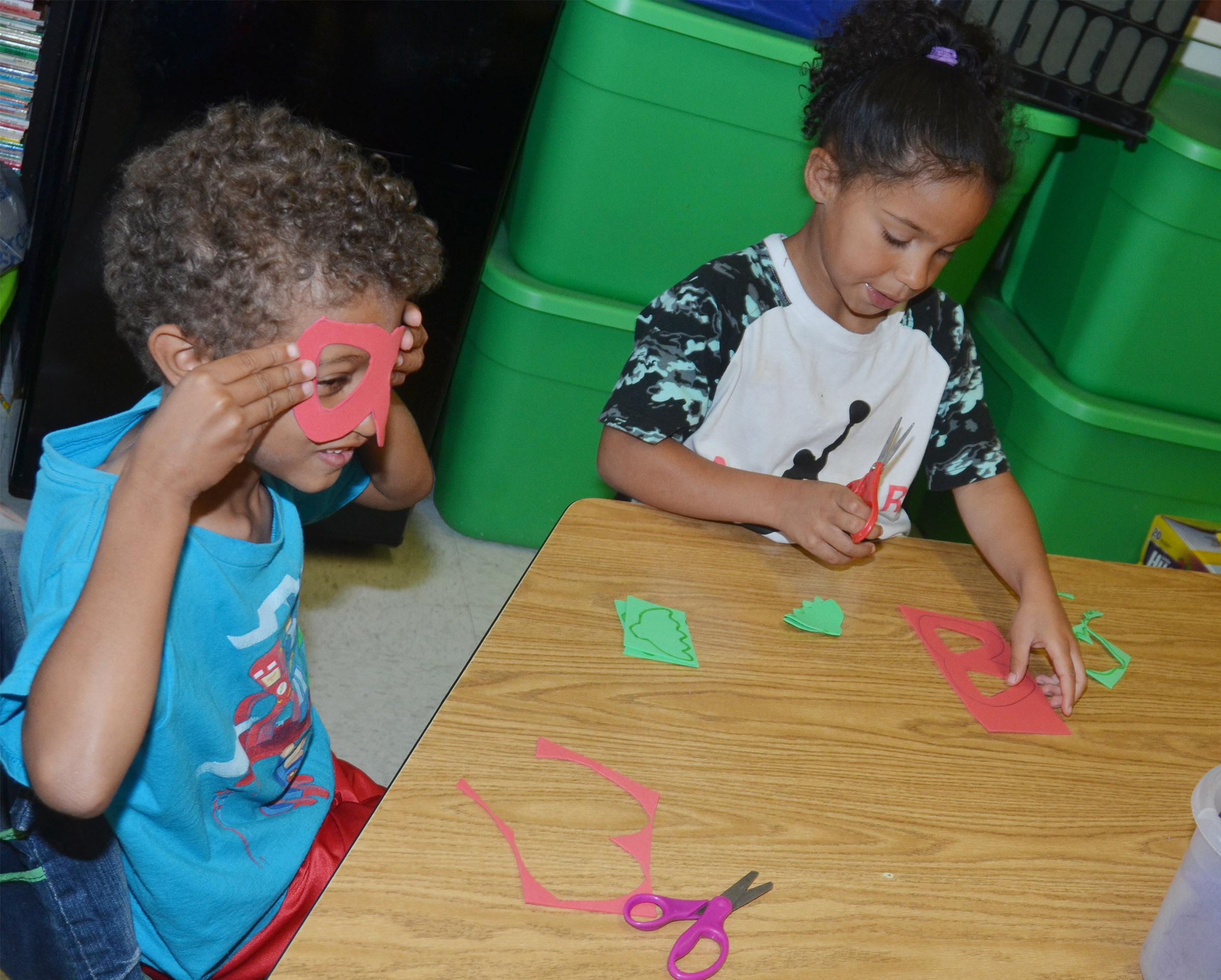 CES kindergartener Tyce Owens tries on his strawberry glasses as classmate Nevaeh Shofner cuts hers out.