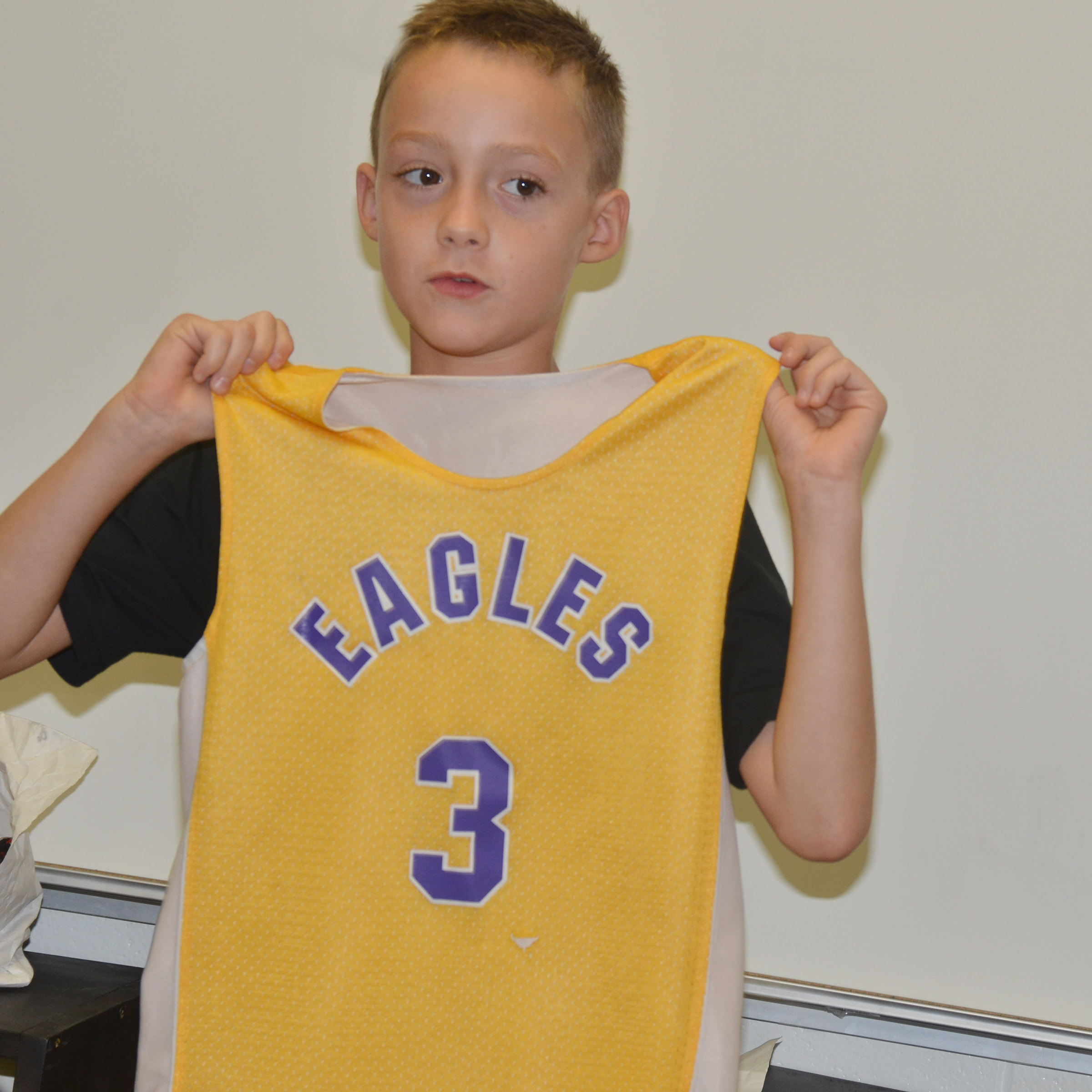 CES fourth-grader Caysen Tungate holds his Eagles basketball jersey.