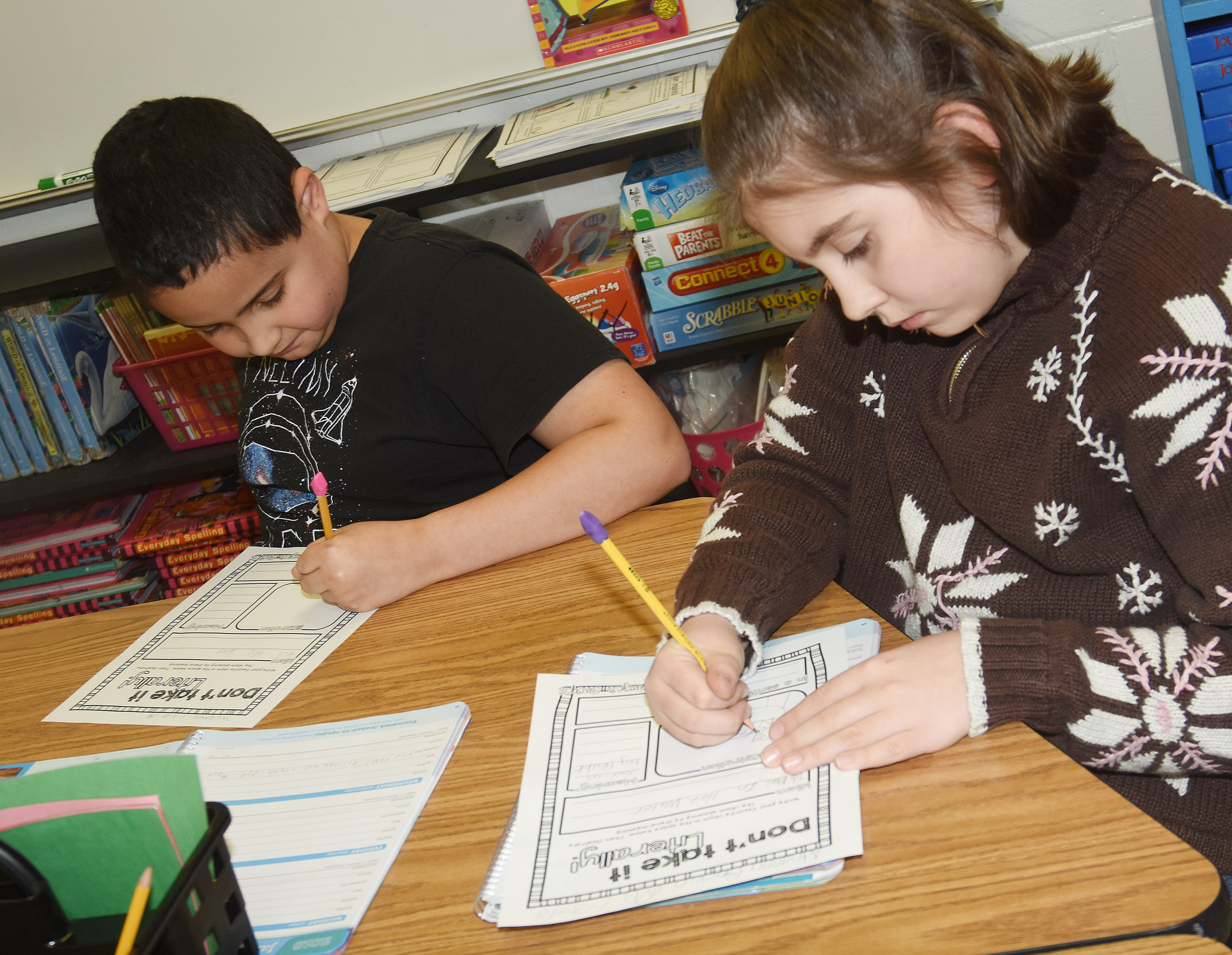 "CES fourth-graders Tayshaun Hickman, at left, and Adrianna Garvin draw picture of their idioms. They wrote about ""hitting the hay"" and ""being in hot water."""