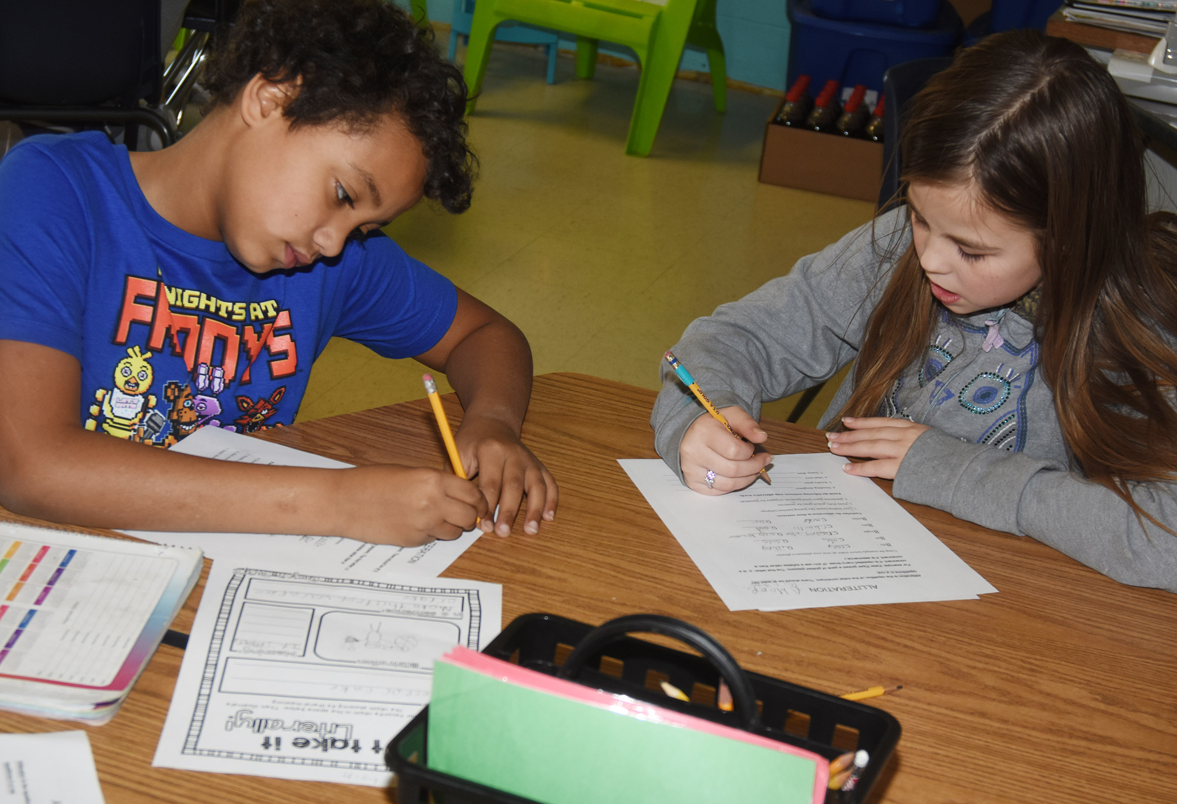 CES fourth-graders Chance Owens, at left, and Chloe Bates write alliterations.