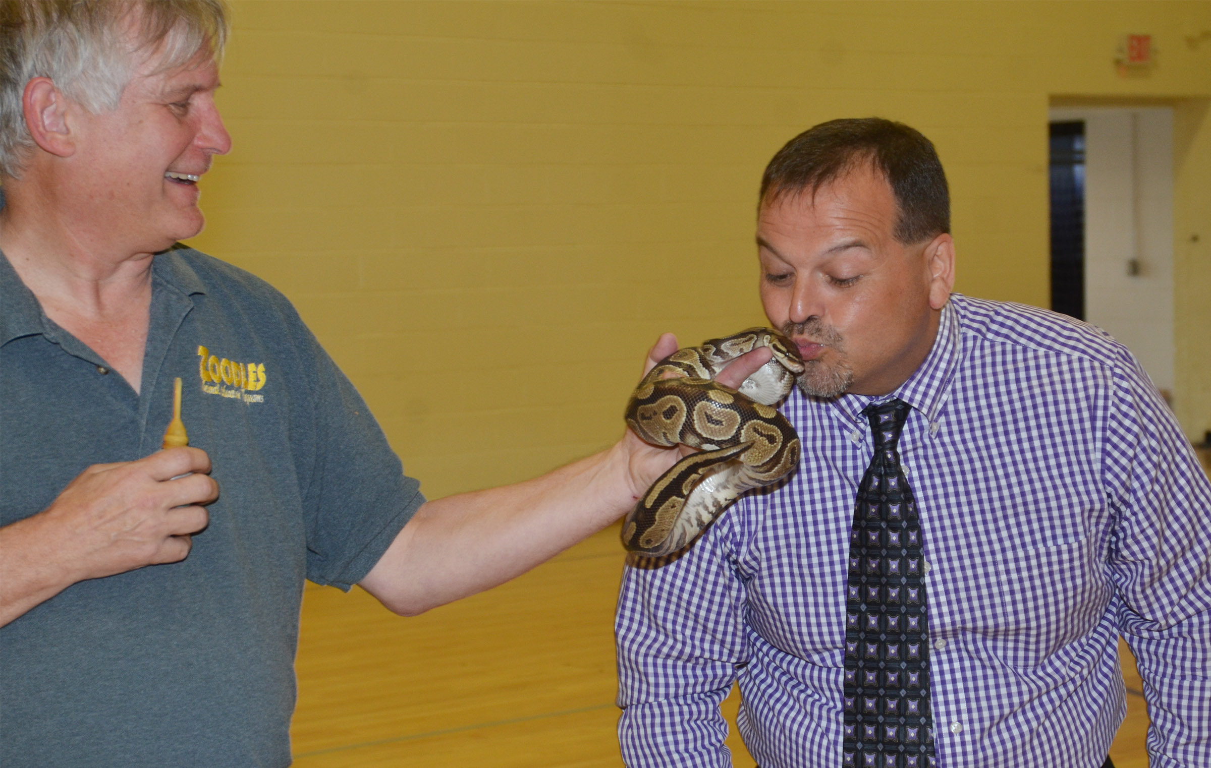 Steven Thomas of Zoodles animal education program holds Barbara the snake as CES Principal Ricky Hunt gives her a kiss.