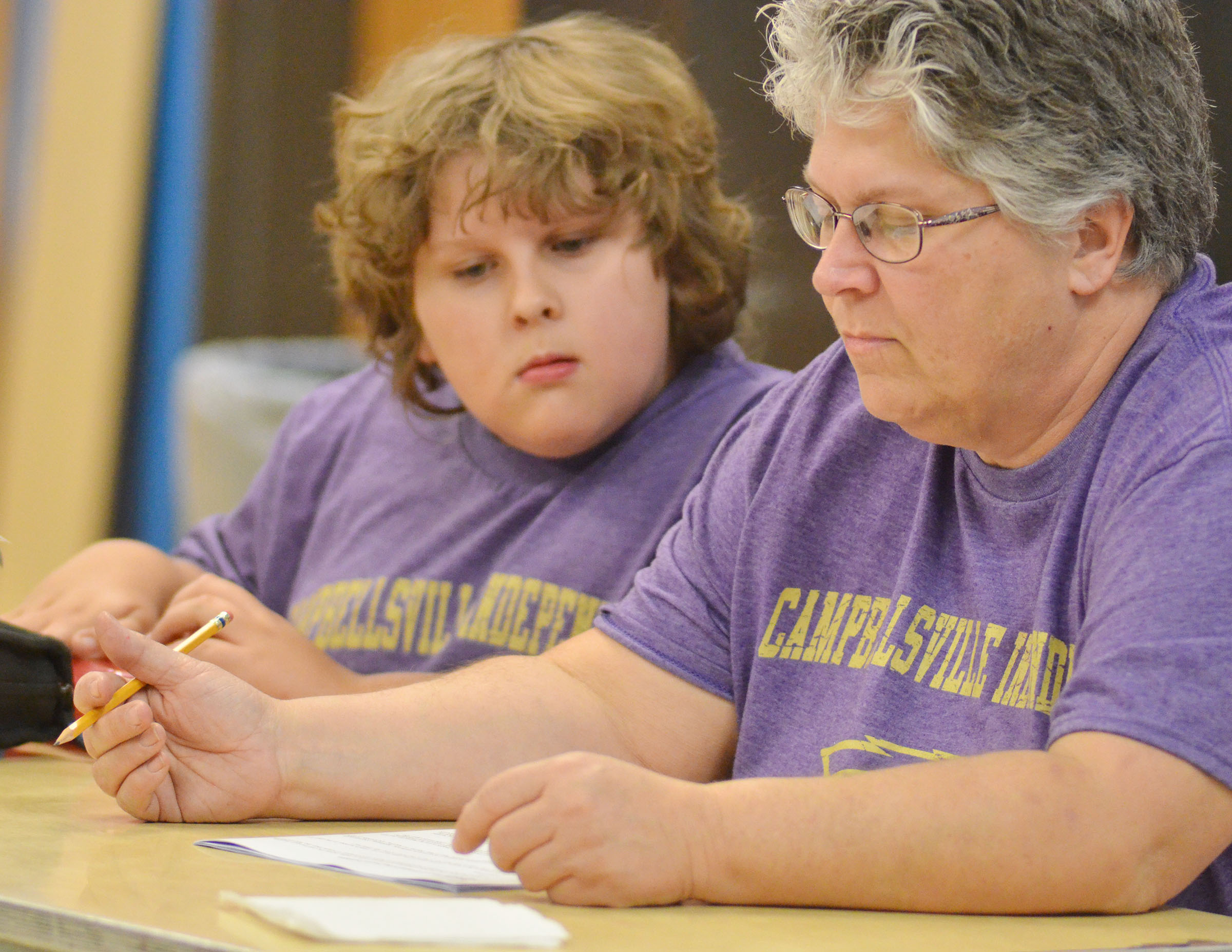 CHS academic team coach Jo Ann Harris reviews quick recall questions as her son, Zeke, a fourth-grader at Campbellsville Middle School, looks on.