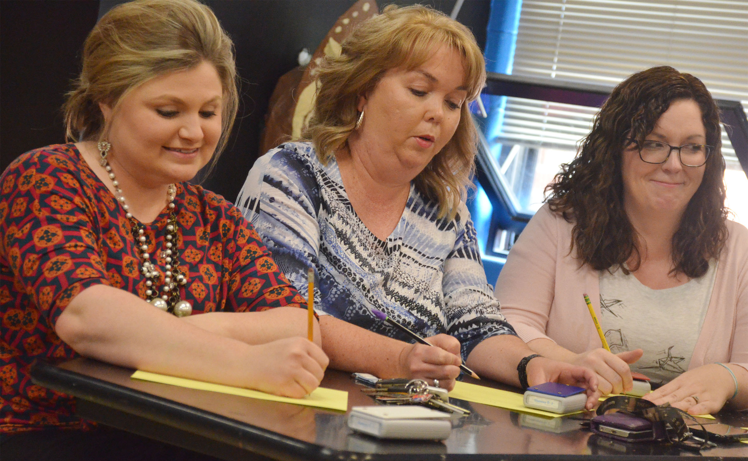 CHS teachers, from left, Lauren Bennett, Sonya Kessler and Lindsay Williams work a math problem.