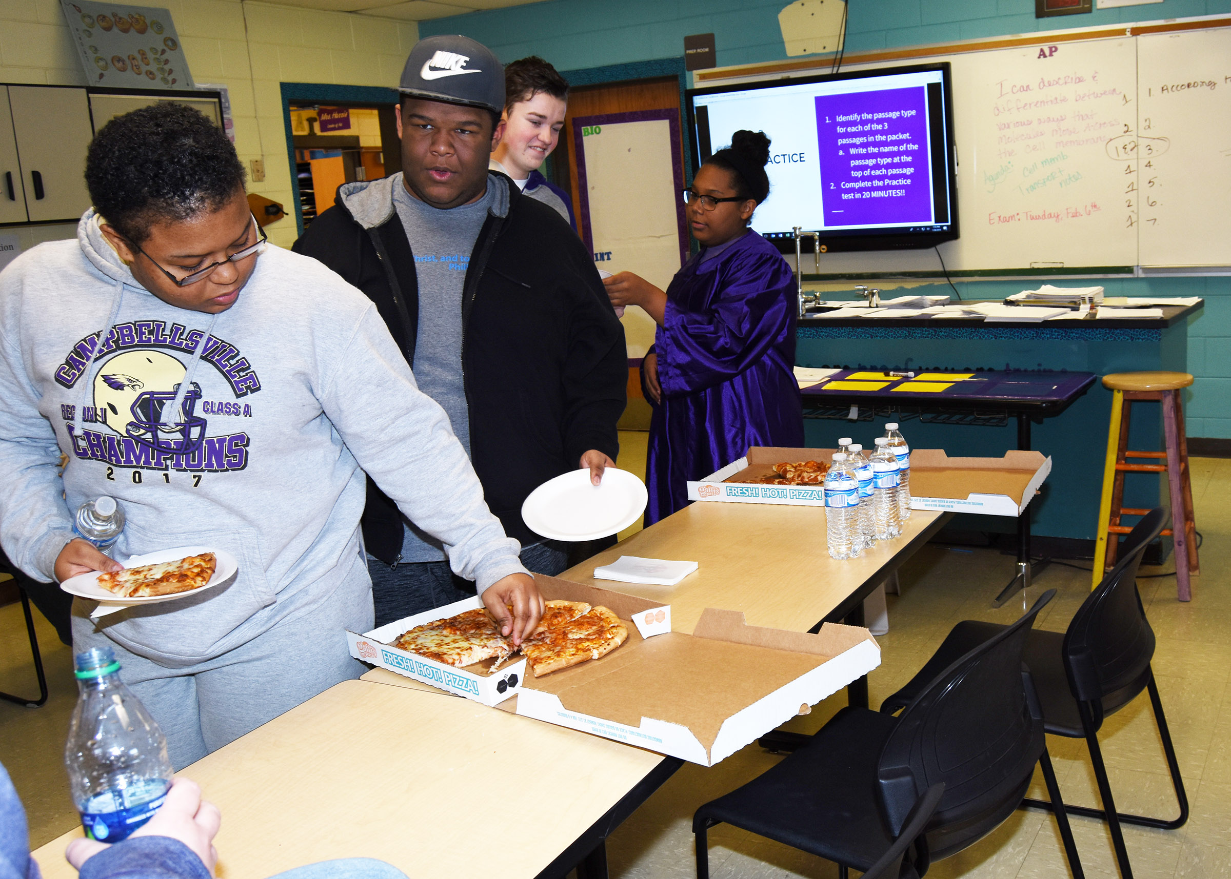CHS students, from left, juniors Natalie Caldwell and Jeremiah Jackson and sophomores Gavin Johnson and Zaria Cowan are served pizza during their ACT workshop.
