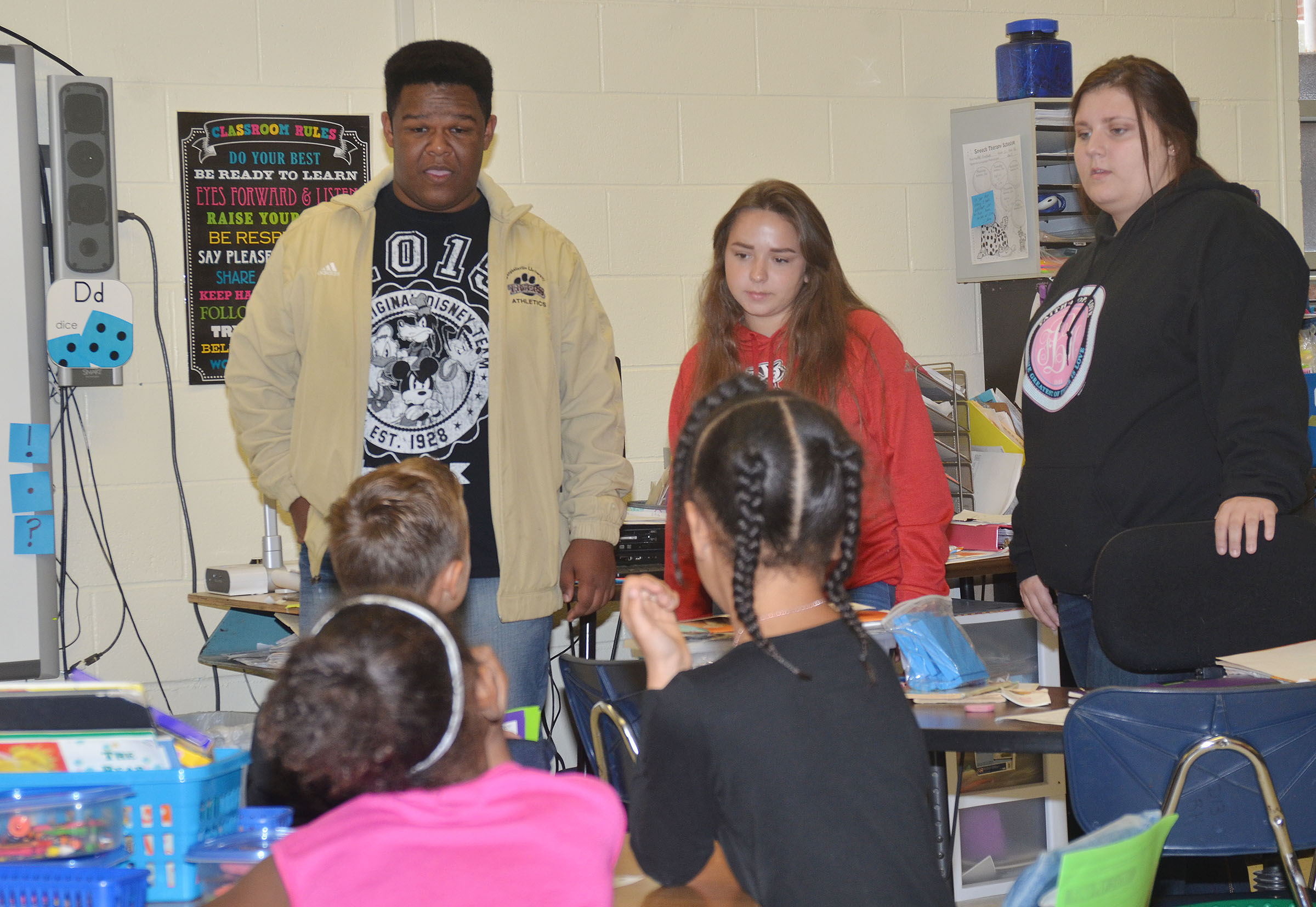 CHS sophomores, from left, Jeremiah Jackson, Christa Riggs and Andrea Bryant talk to CES second-graders about government.