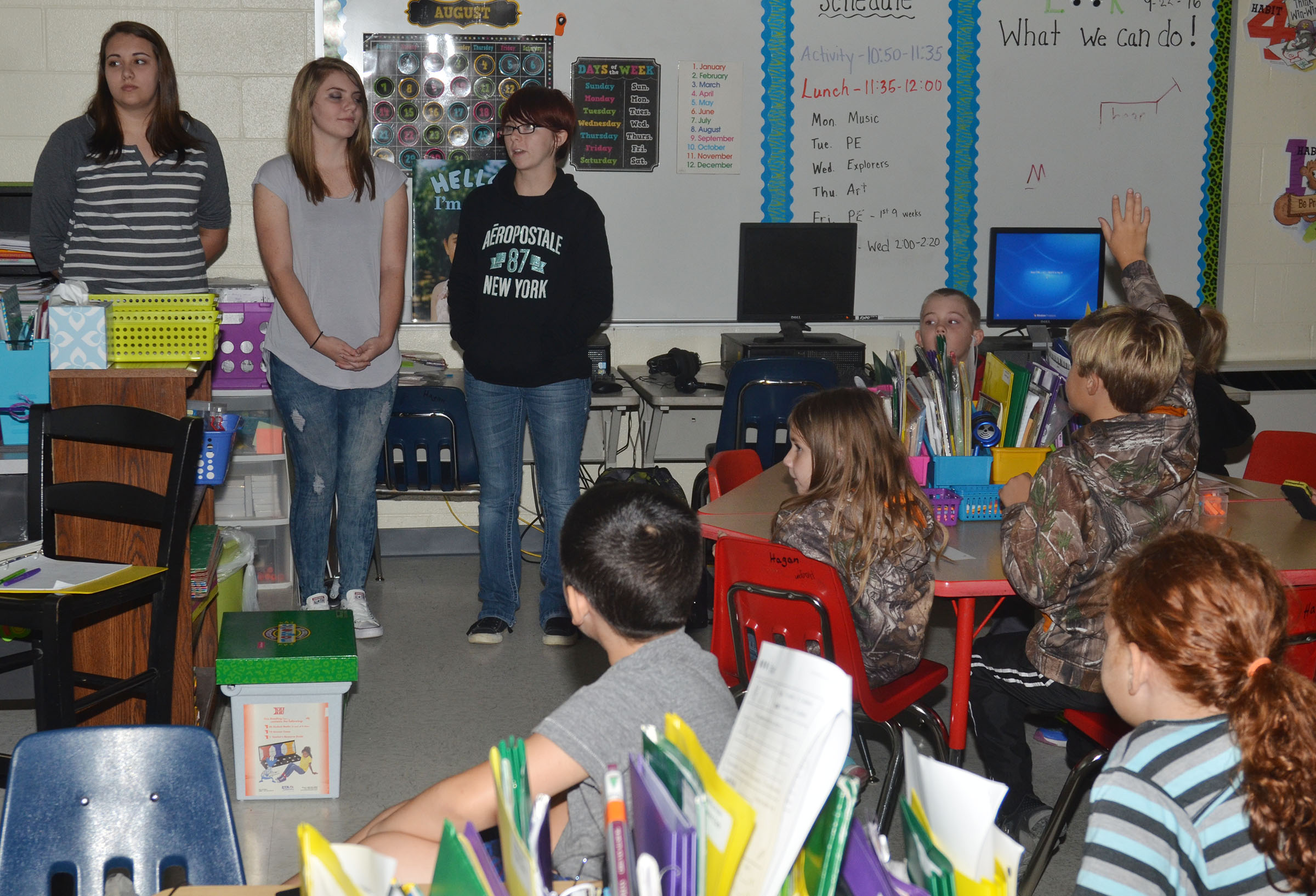 CHS sophomores, from left, Elizabeth Sullivan, Hayley Stapleton and Christina Phipps talk to CES second-graders about government.