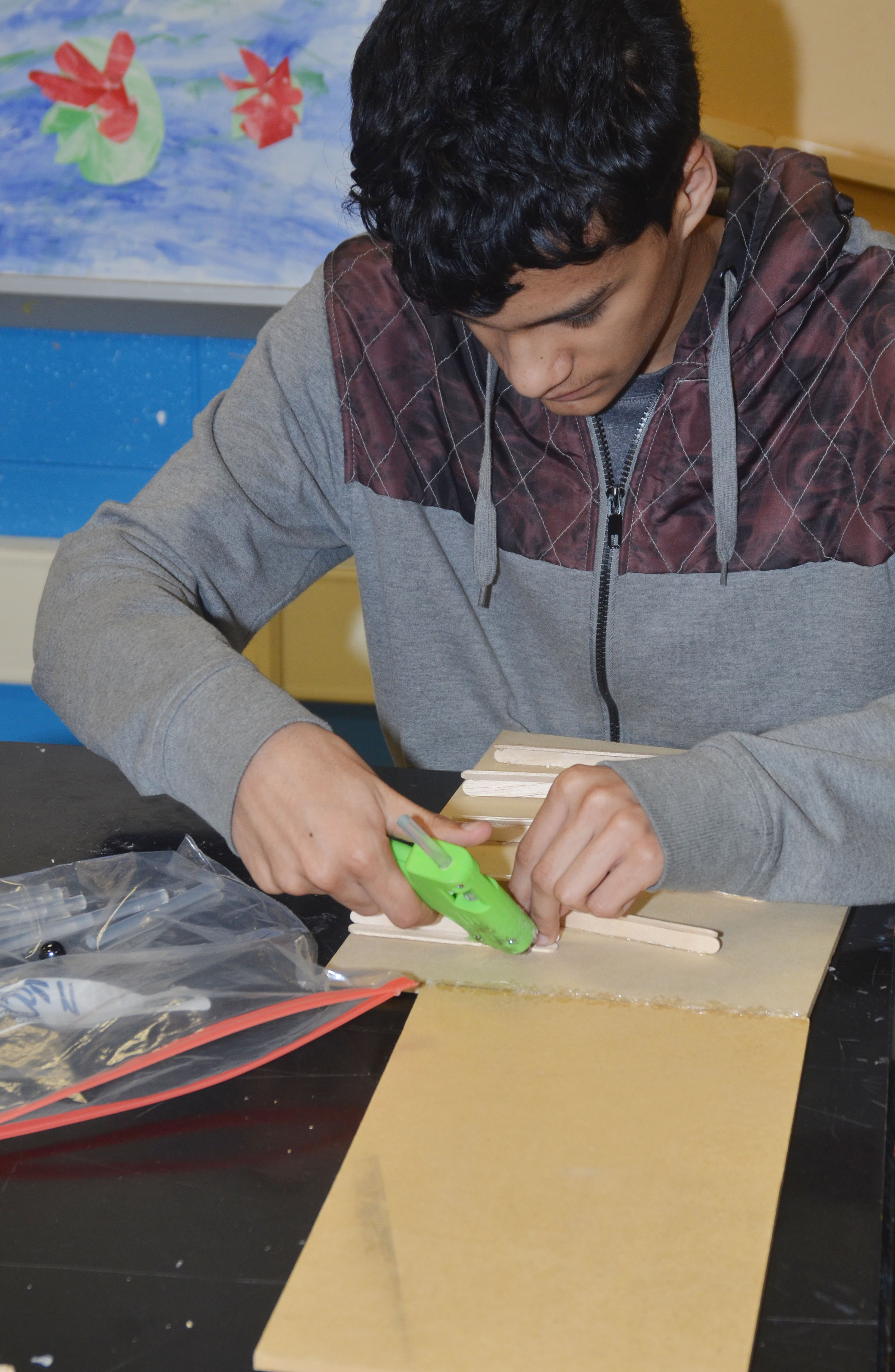 CHS freshman Ben Arachi glues Popsicle sticks together to make his ball dropper.