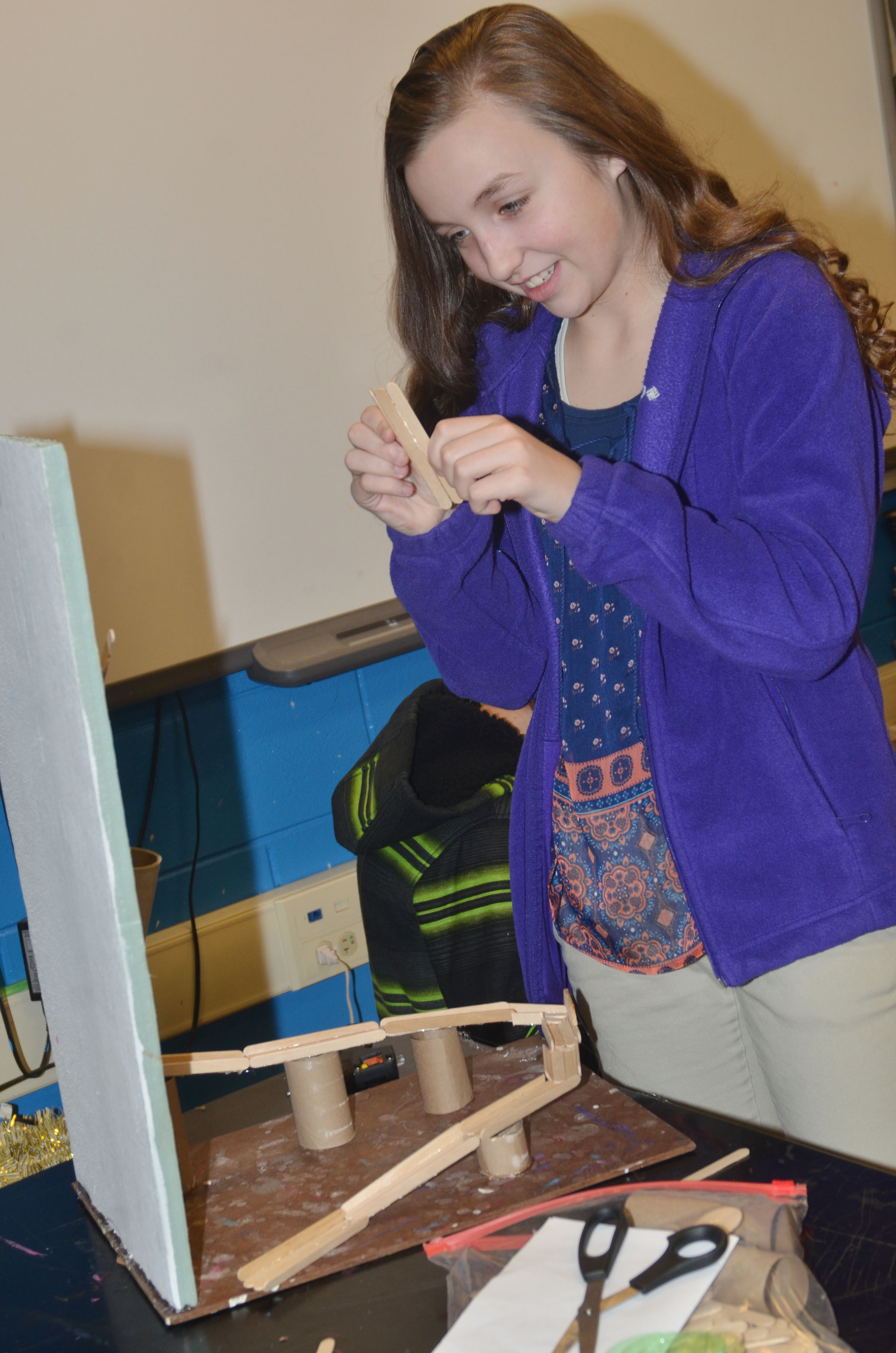 Campbellsville Middle School seventh-grader Lainey Watson glues Popsicle sticks together as she makes her ball dropper.