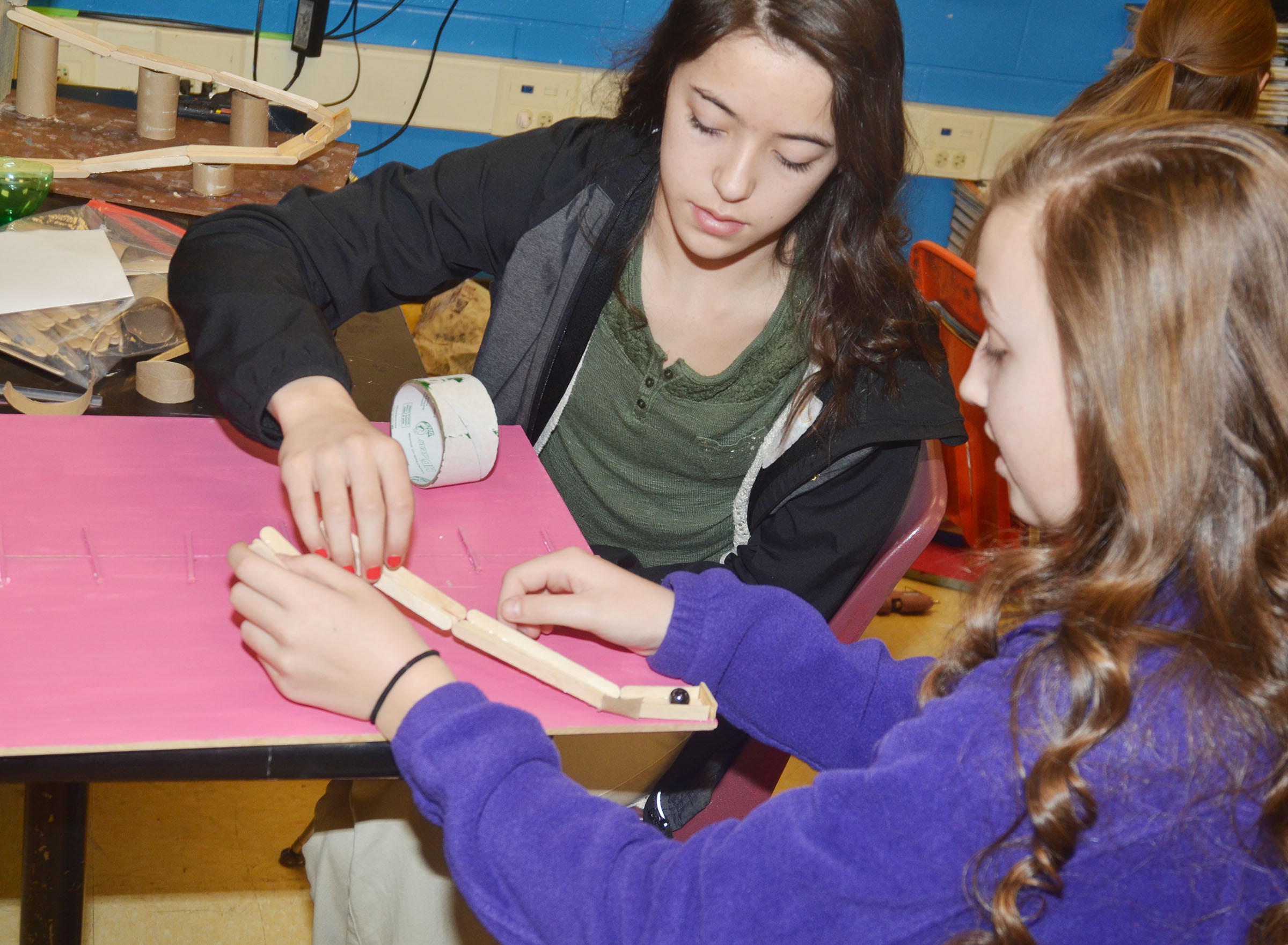 Campbellsville Middle School seventh-graders Kaylyn Smith, at left, and Lainey Watson work together to build their ball dropper machine.