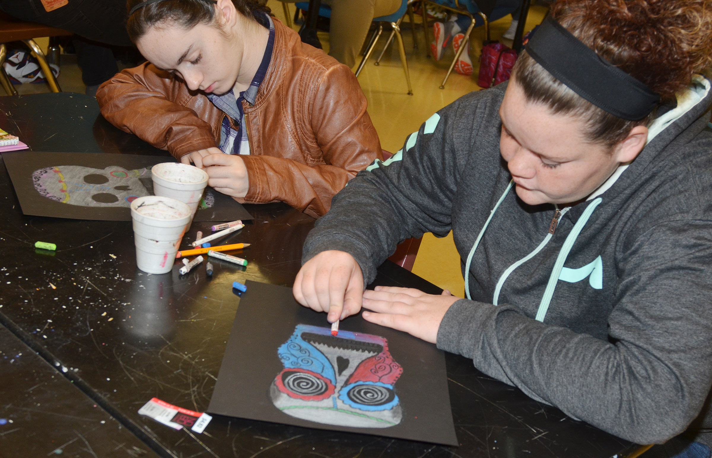 CHS sophomores Jewell Cox, at left, and Shallan Philpott put finishing touches on their Day of the Dead skulls.