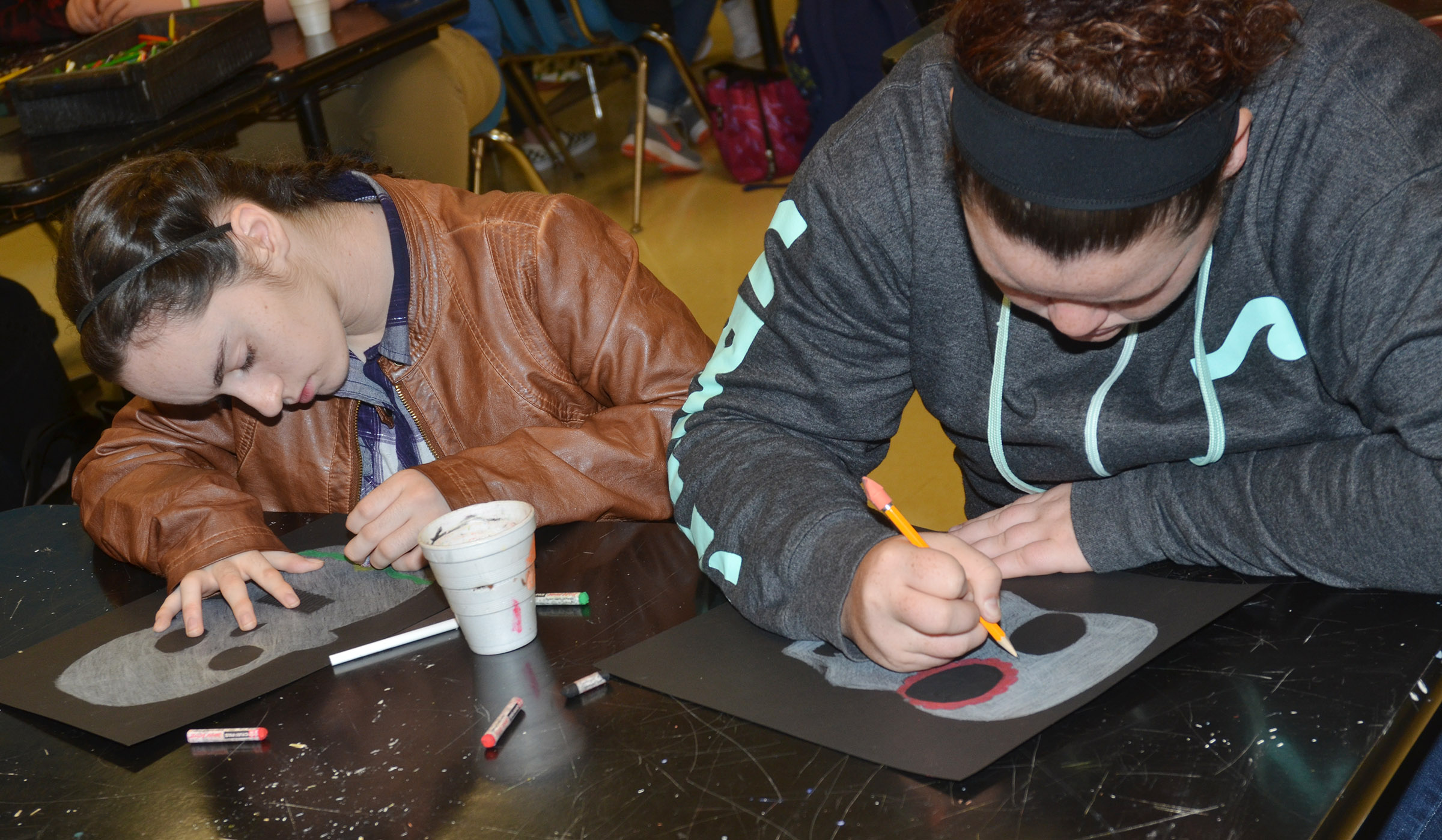 CHS sophomores Jewell Cox, at left, and Shallan Philpott color their Day of the Dead skulls.
