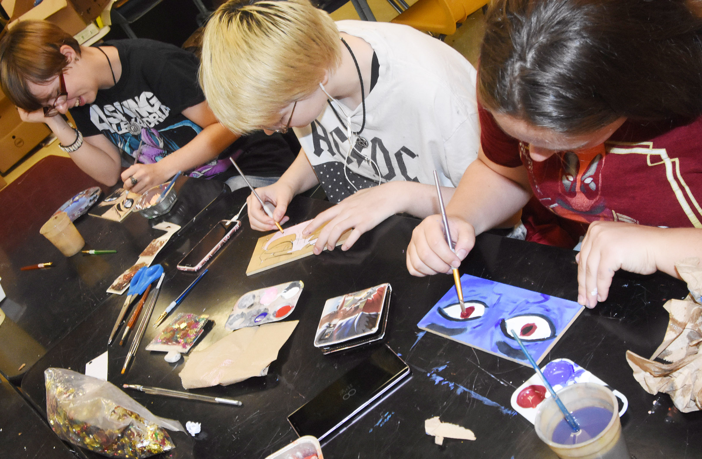 From left, CHS seniors Christina Phipps, Chloe Decker and Ruby Hatfield paint their eyes.