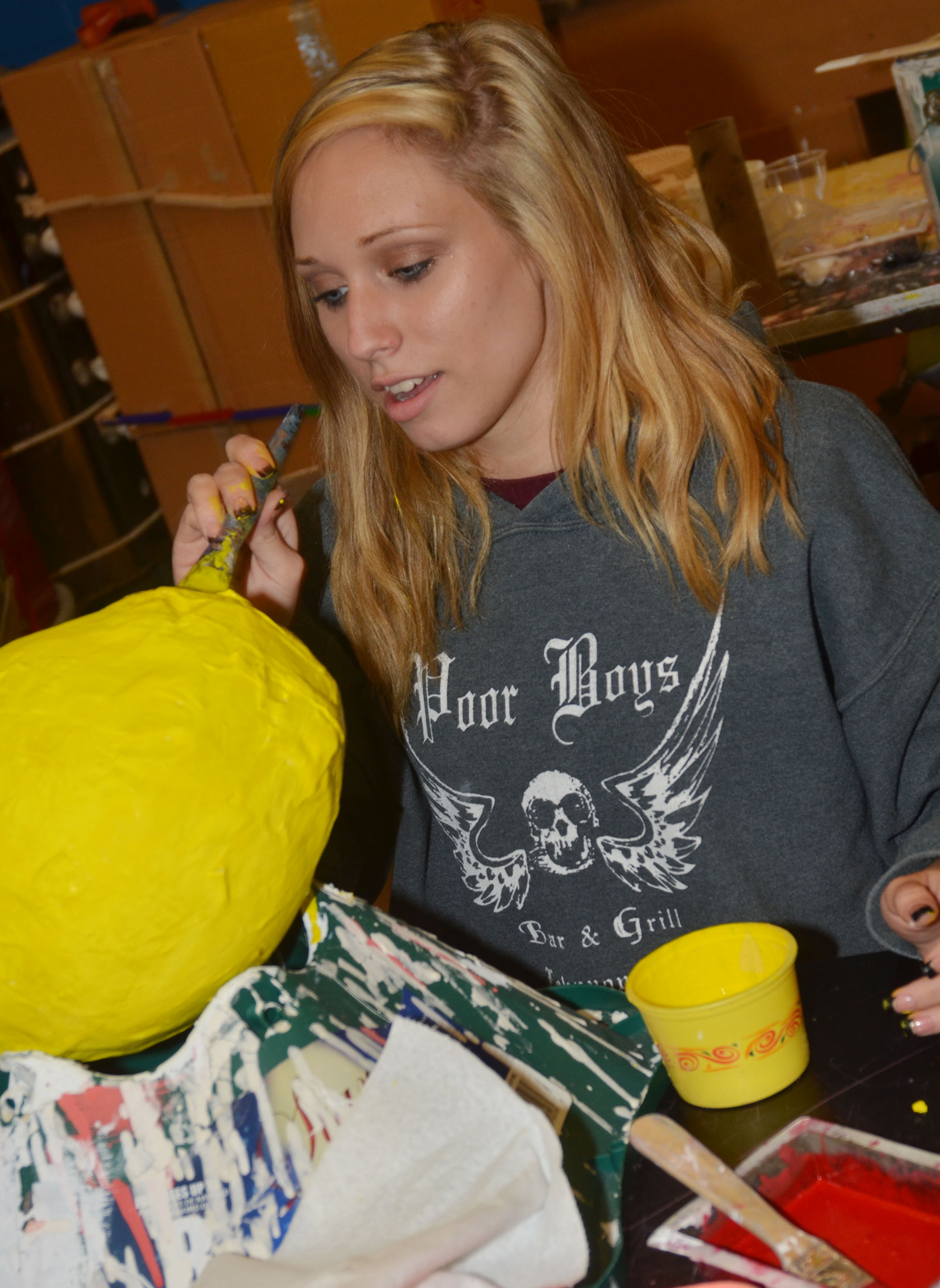 CHS junior Jasmine Coomer paints her final art project, a paper mache figure.