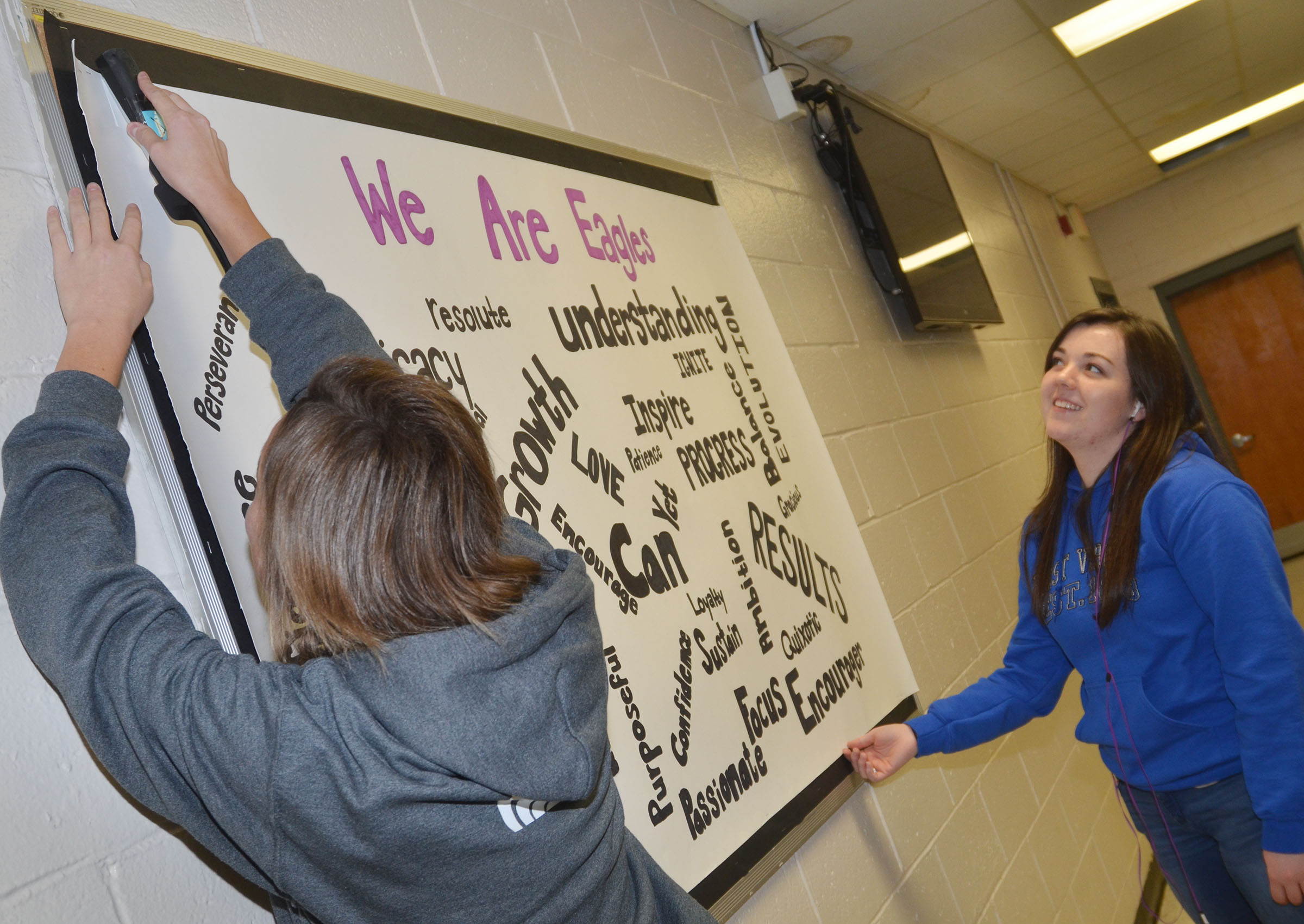 CHS seniors Kyrsten Hill, at left, and Tiffany Stagner hang the inspirational poster they made for their classmates.
