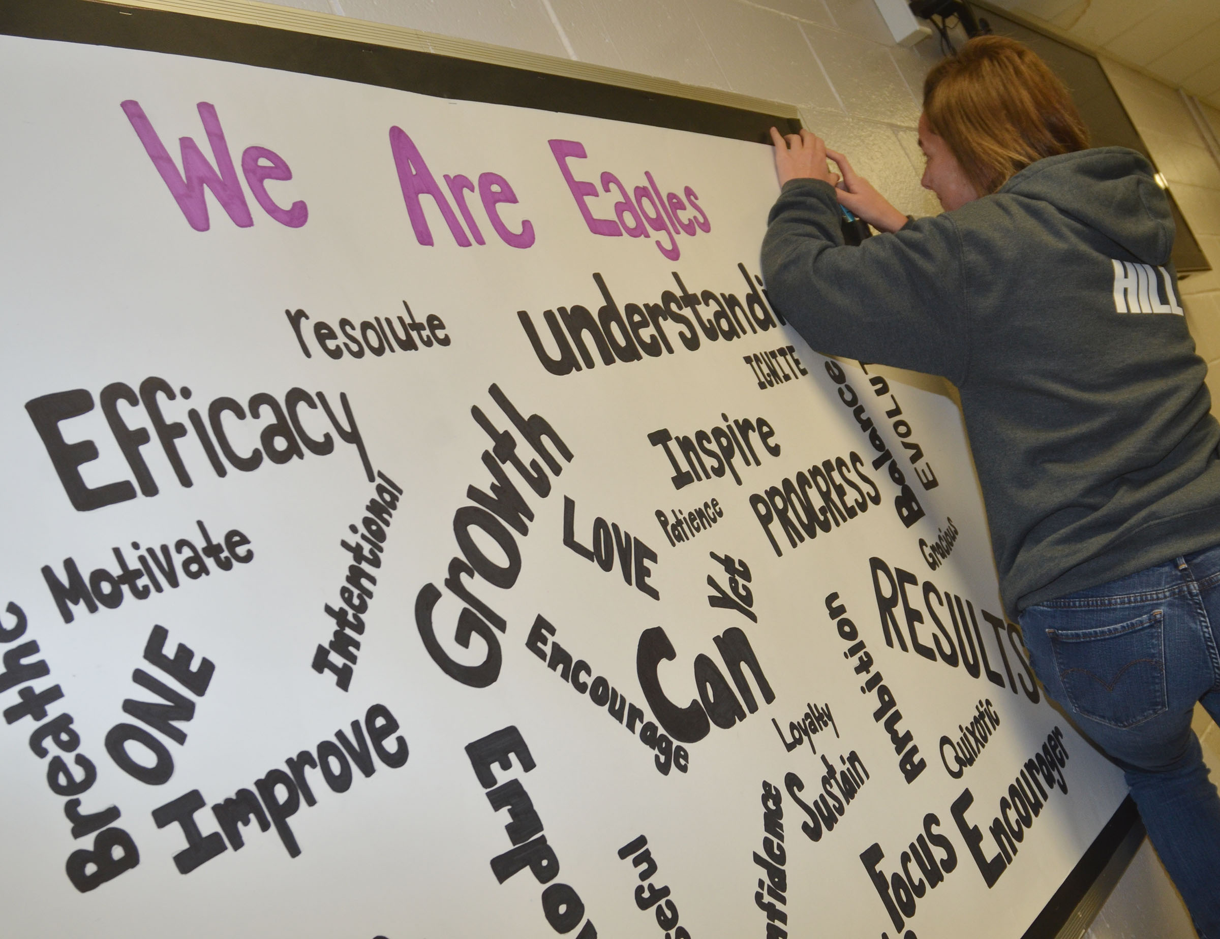 CHS senior Kyrsten Hill hangs the inspirational poster she and classmate Tiffany Stagner made for their classmates.