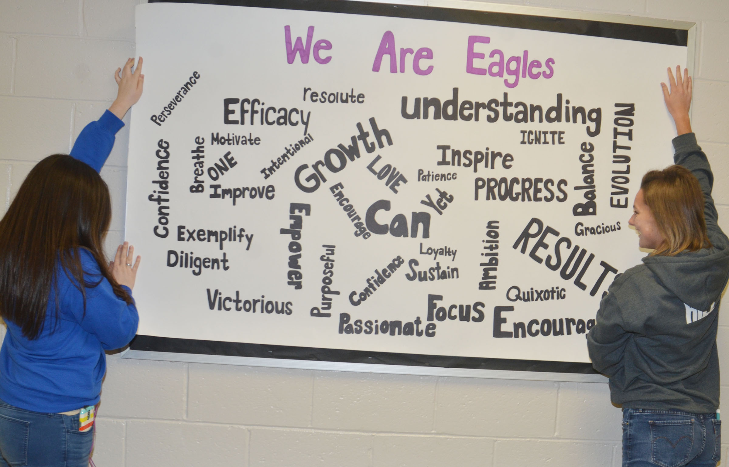 CHS seniors Tiffany Stagner, at left, and Kyrsten Hill hang the inspirational poster they made for their classmates.