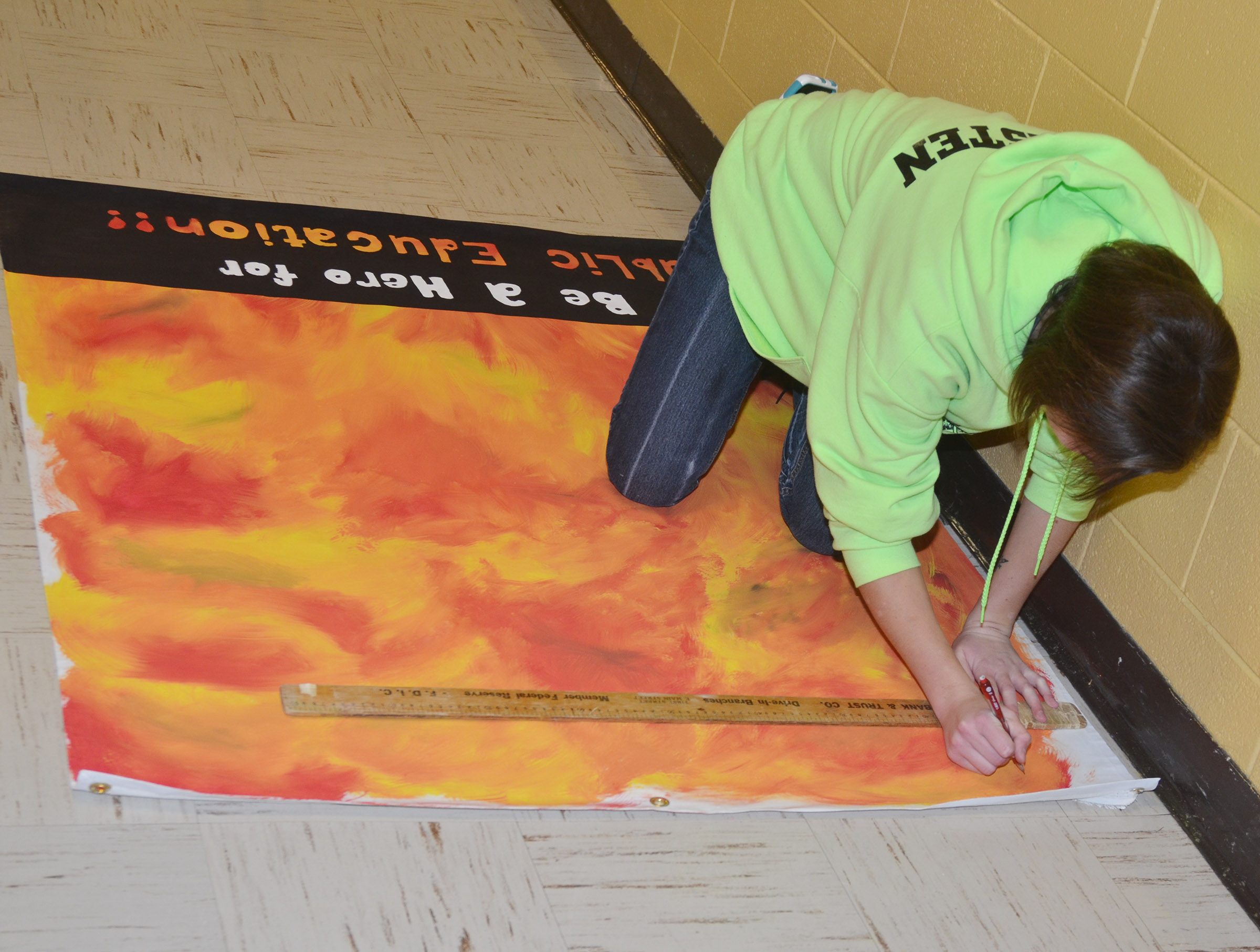 "CHS National Art Honor Society member Kyrsten Hill, a senior, is making a banner for display at the KSBA annual conference, with the theme ""Be a superhero for Public education."""