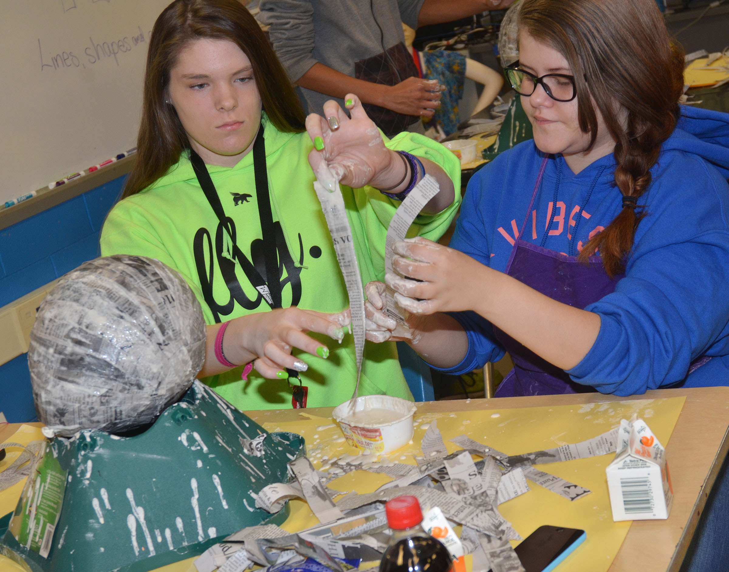CHS sophomores Cassie Pipes, at left, and Caylee Shofner dip their newspaper strips into the paper mache mixture.