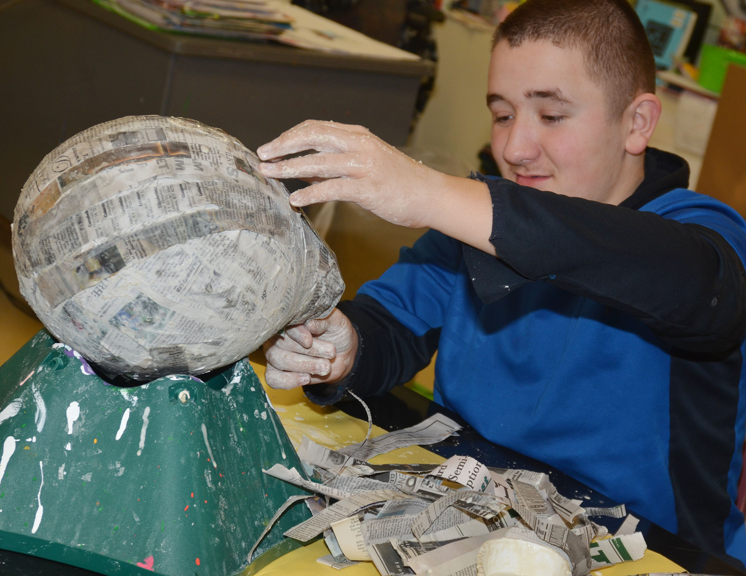 Campbellsville Middle School eighth-grader Zachary Shaw adds newspaper to his 3D sculpture.