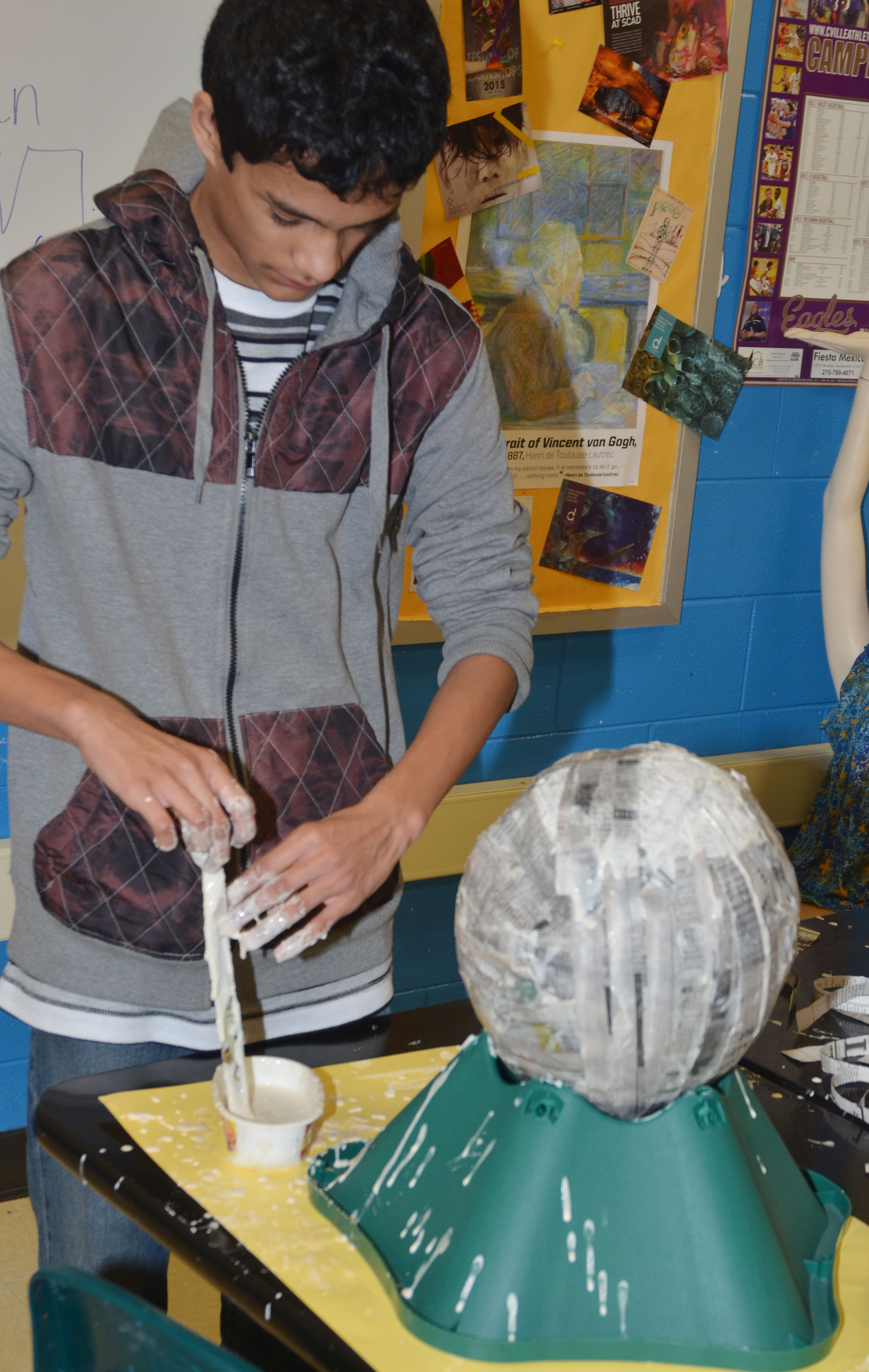CHS freshman Ben Arachi dips his newspaper into the paper mache mixture.