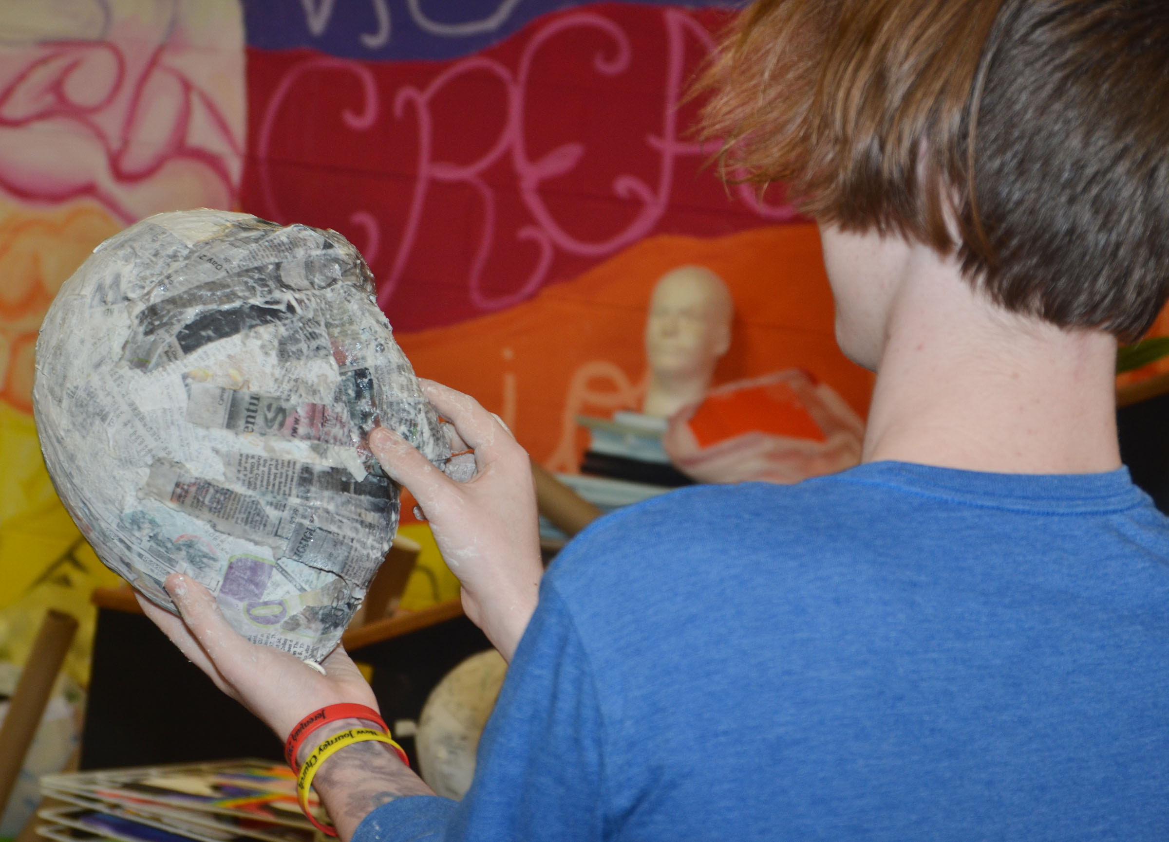 CHS sophomore Jason Agee takes a look at the facial features on his 3D paper mache project.