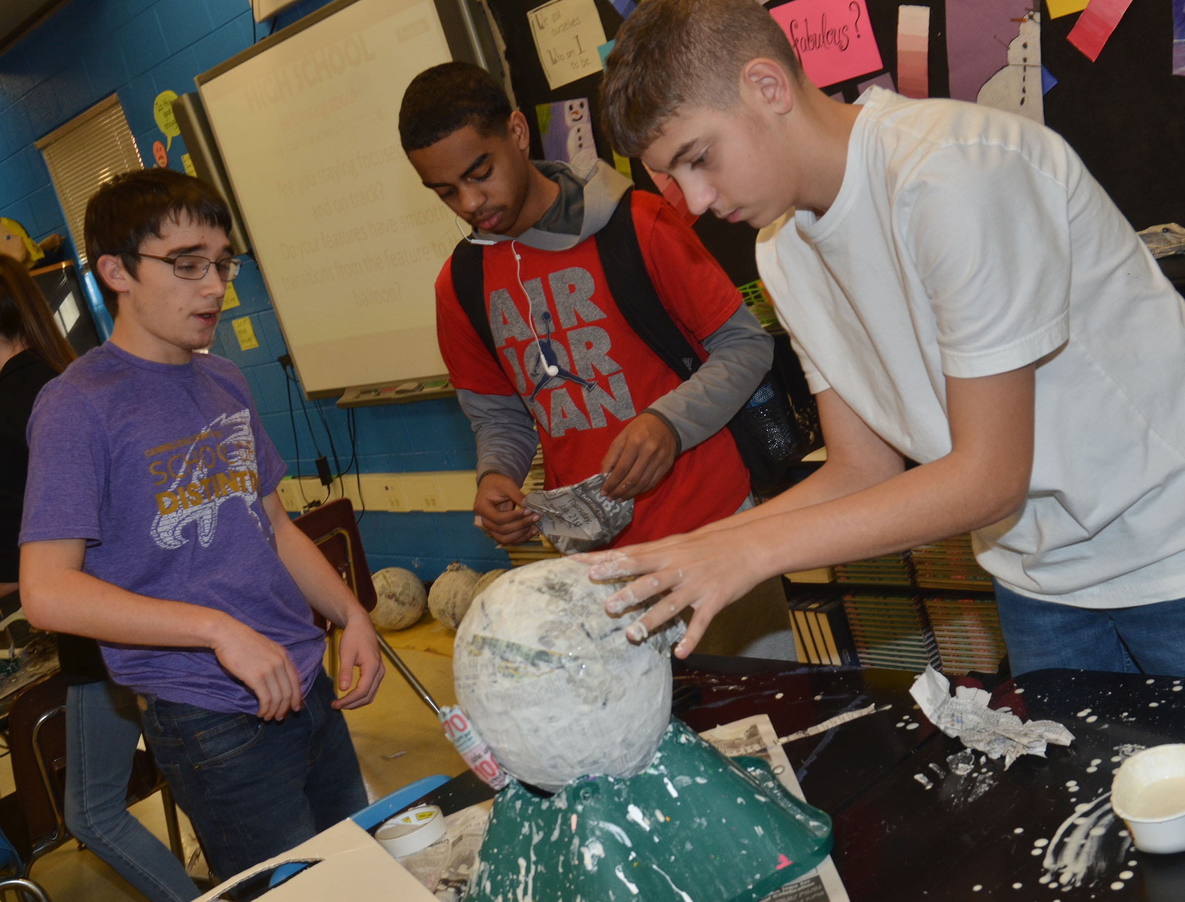 From left, CHS sophomores Skyler Burchett, Davon Cecil and Casey Hardin shape their 3D paper mache project.