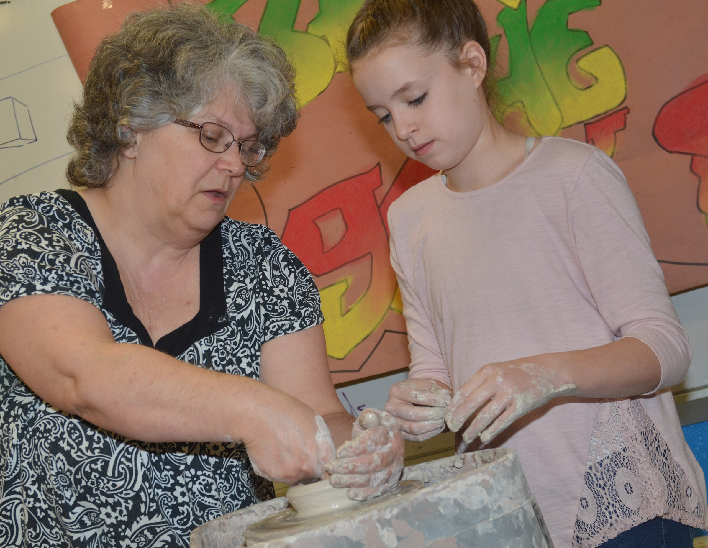CHS art teacher Jo Ann Harris helps Campbellsville Middle School seventh-grader Rylee Petett as she uses the potter's wheel for the first time.