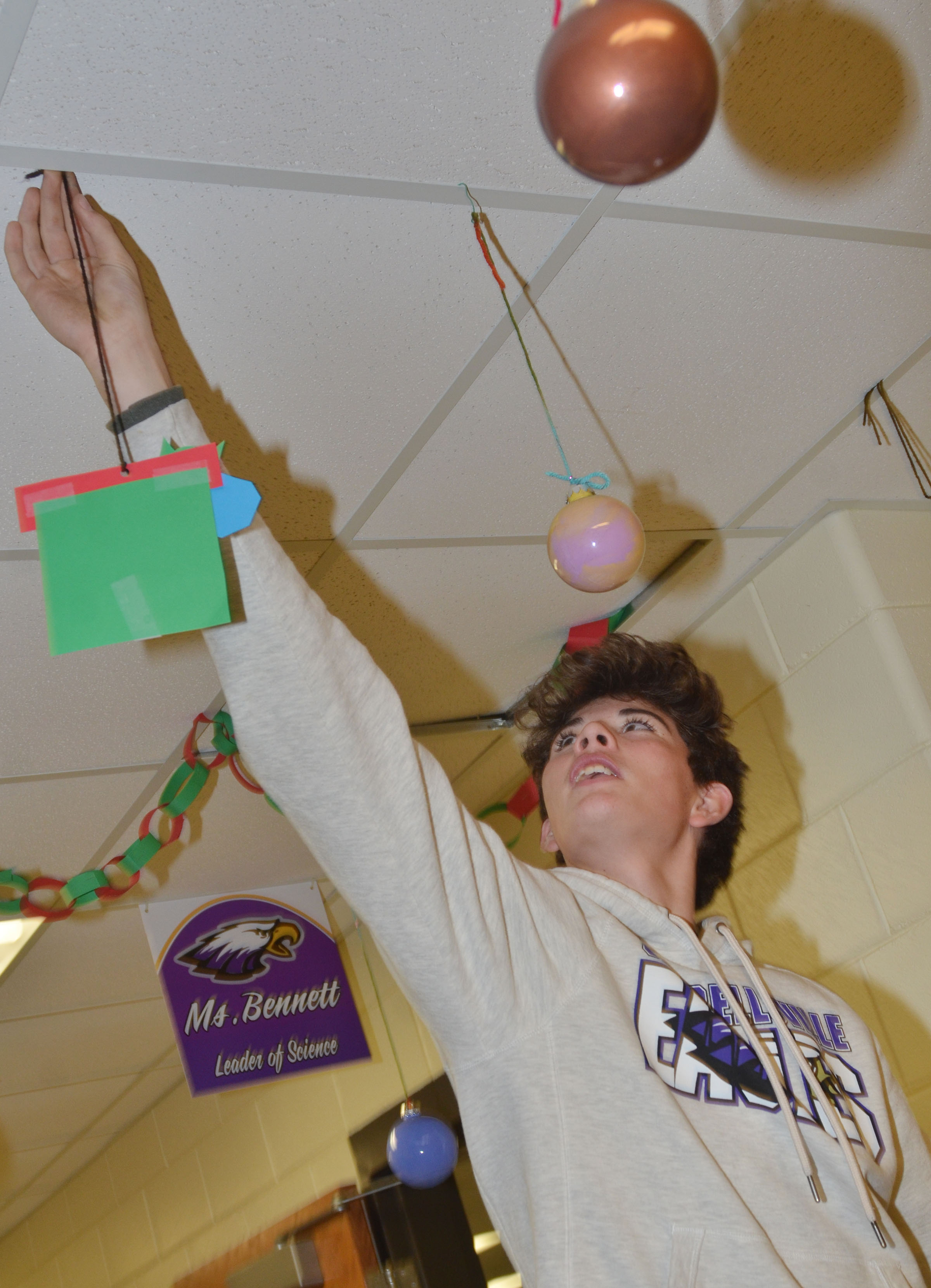CHS freshman Mark Rigsby hangs a Christmas ornament.