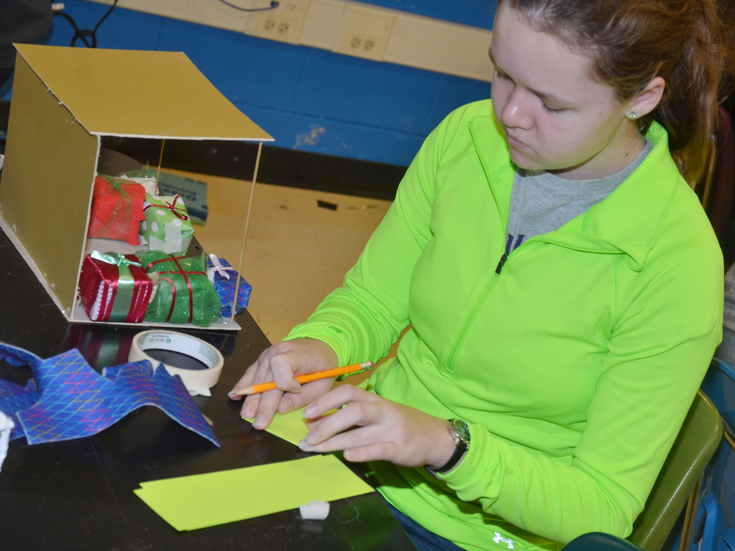 Campbellsville Middle School seventh-grader MaCayla Falls creates a miniature model of her set design.