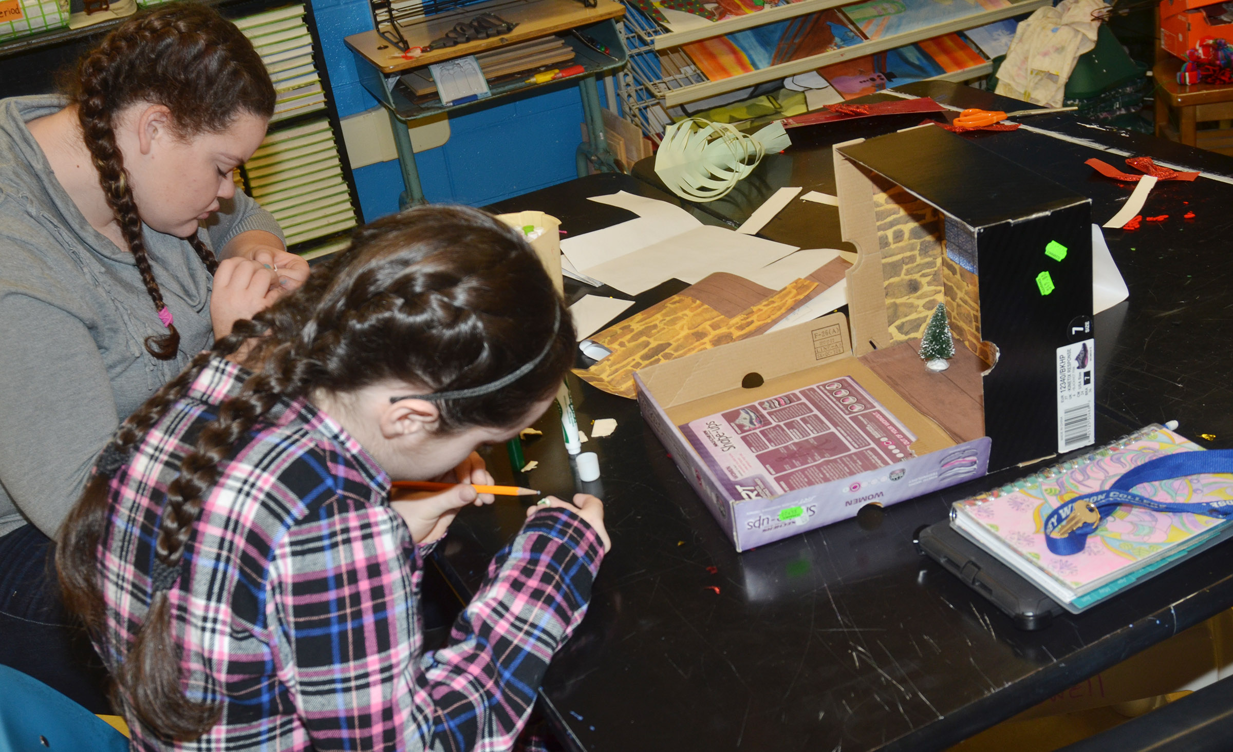 CHS sophomores Shallan Philpott, at left, and Jewell Cox work on a miniature model of their set design.