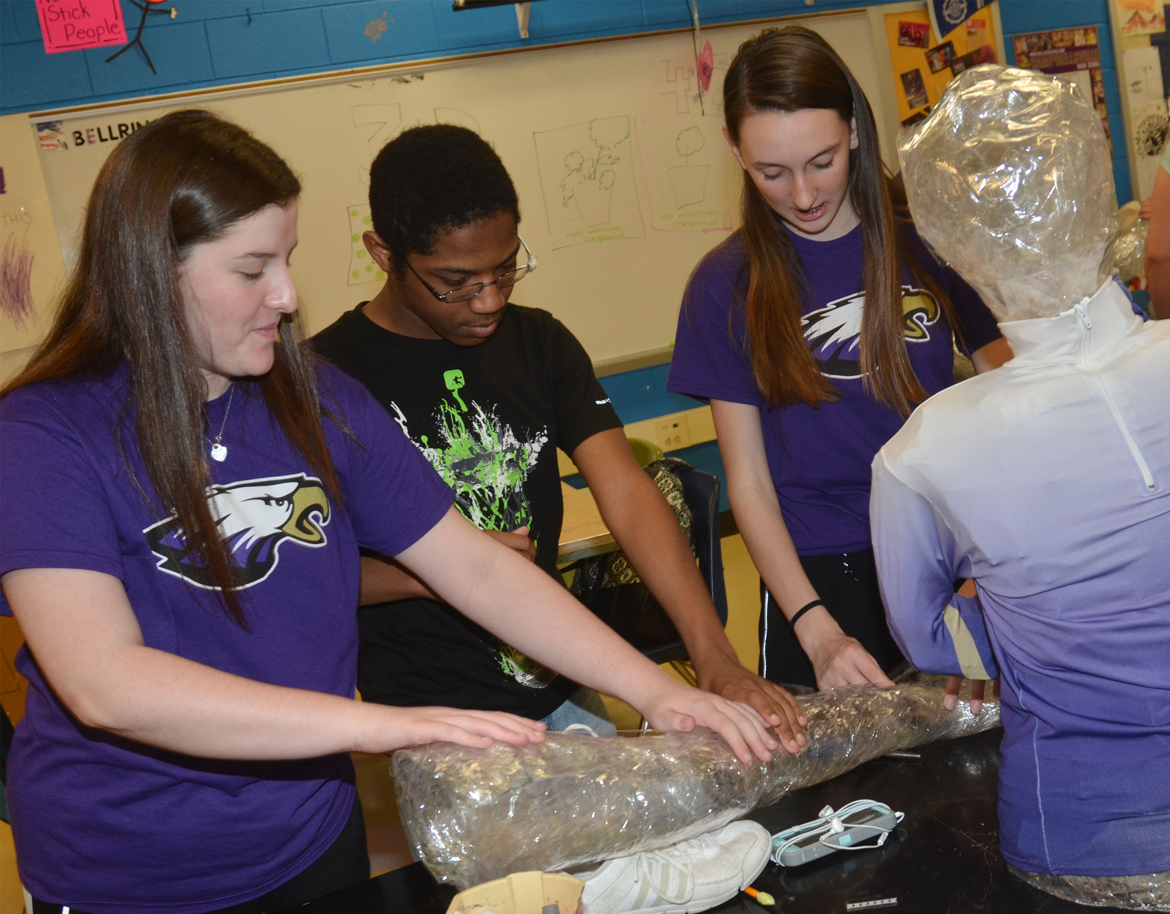 From left, CHS freshman Alli Wilson, sophomore Travis Nash and freshman Zoe McAninch put their tape person together.