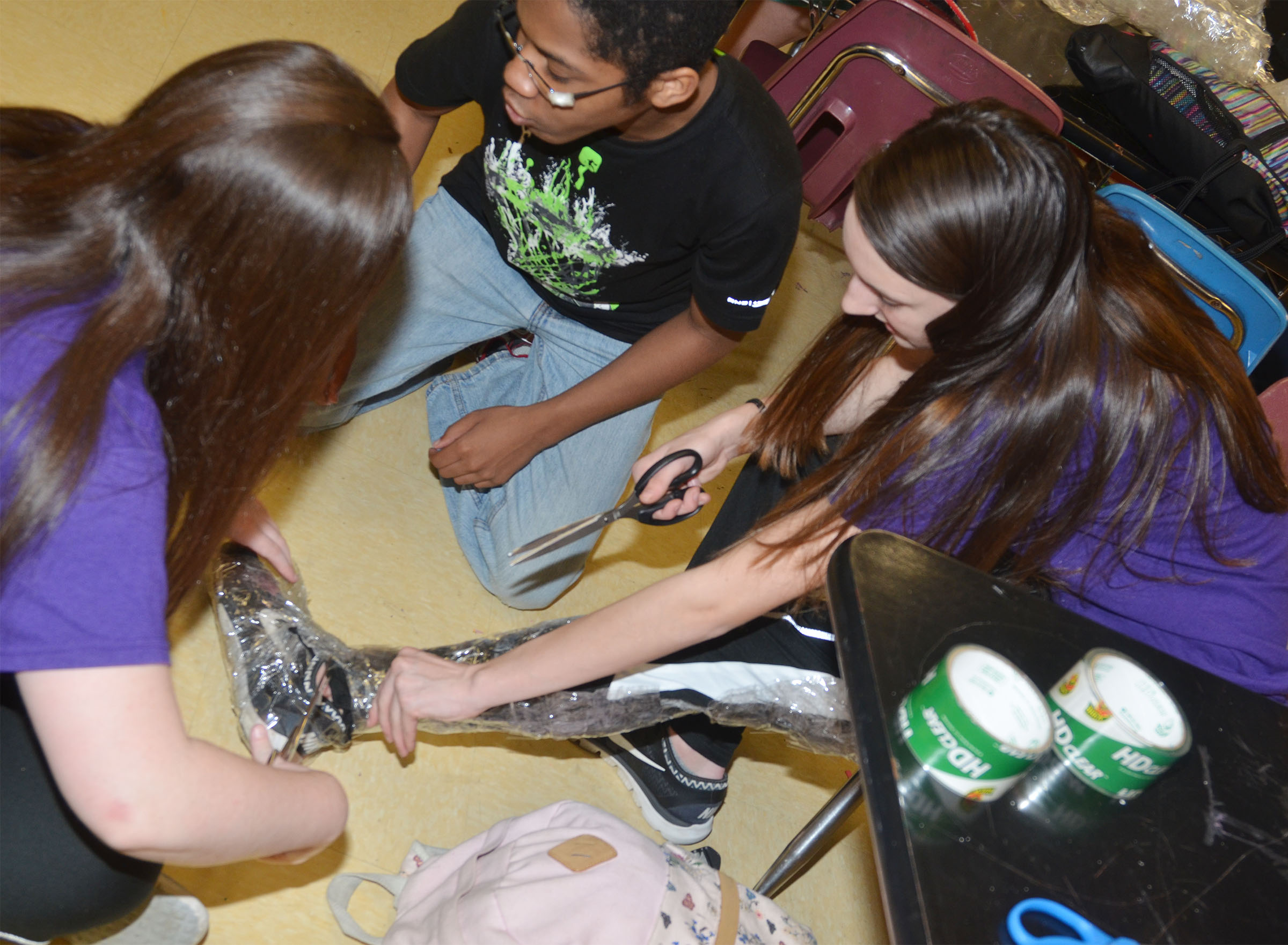 CHS freshman Zoe McAninch is taped, with some help from classmate Alli Wilson and sophomore Travis Nash.