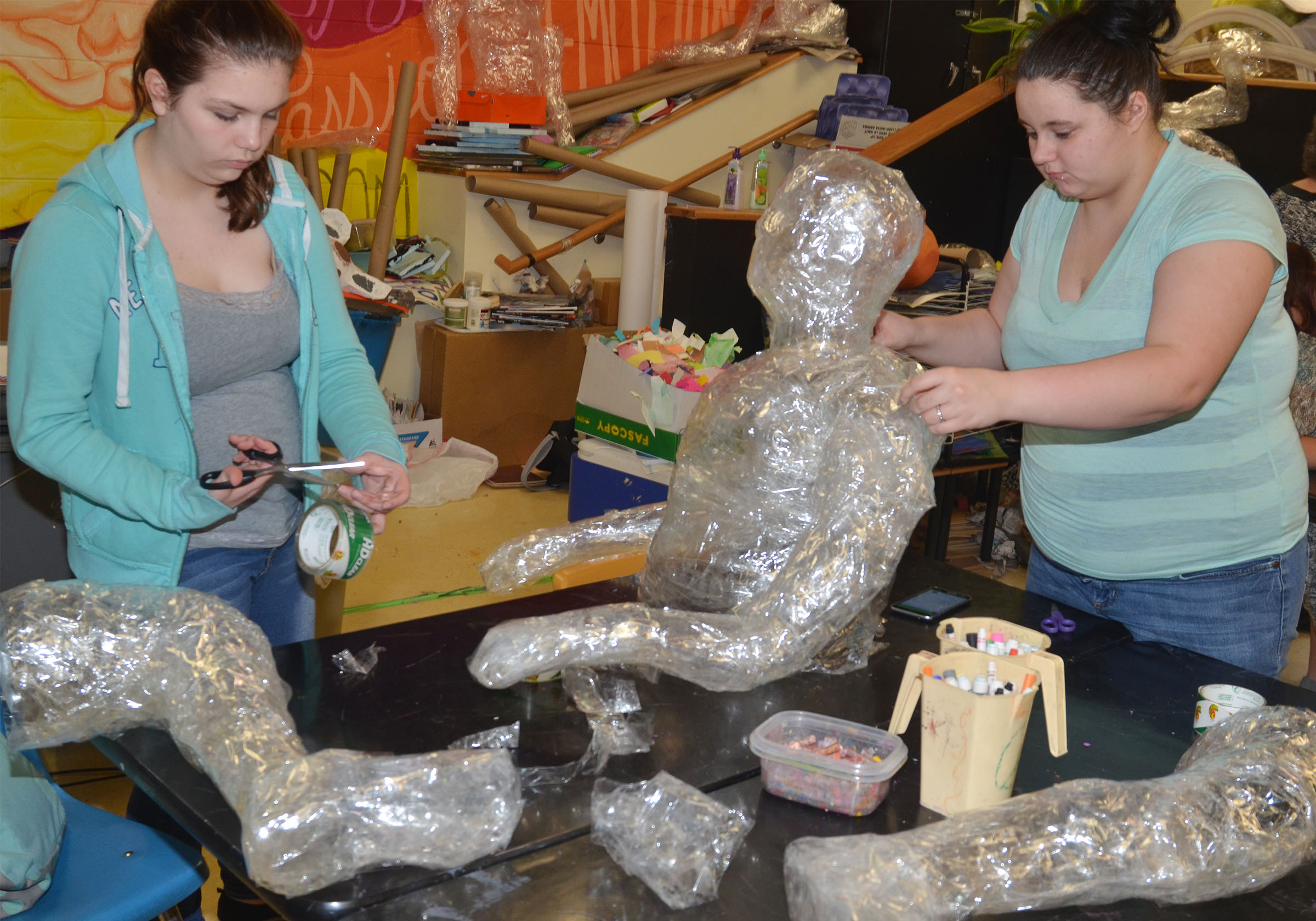 CHS freshman Shelby Hunt, at left, and sophomore Amanda Dotson put their tape person together.