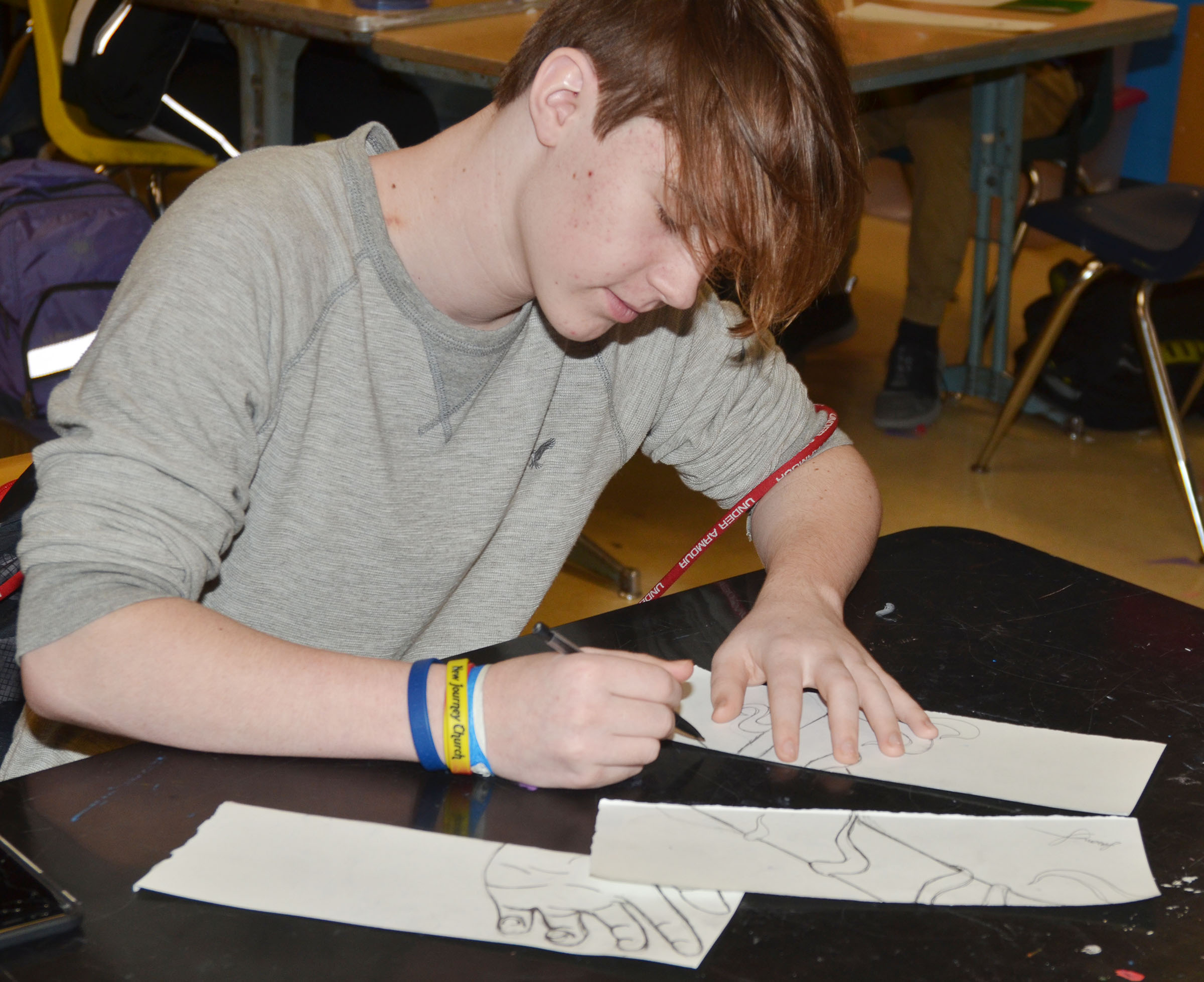 CHS sophomore Jason Agee draws his design for his triptych panels.