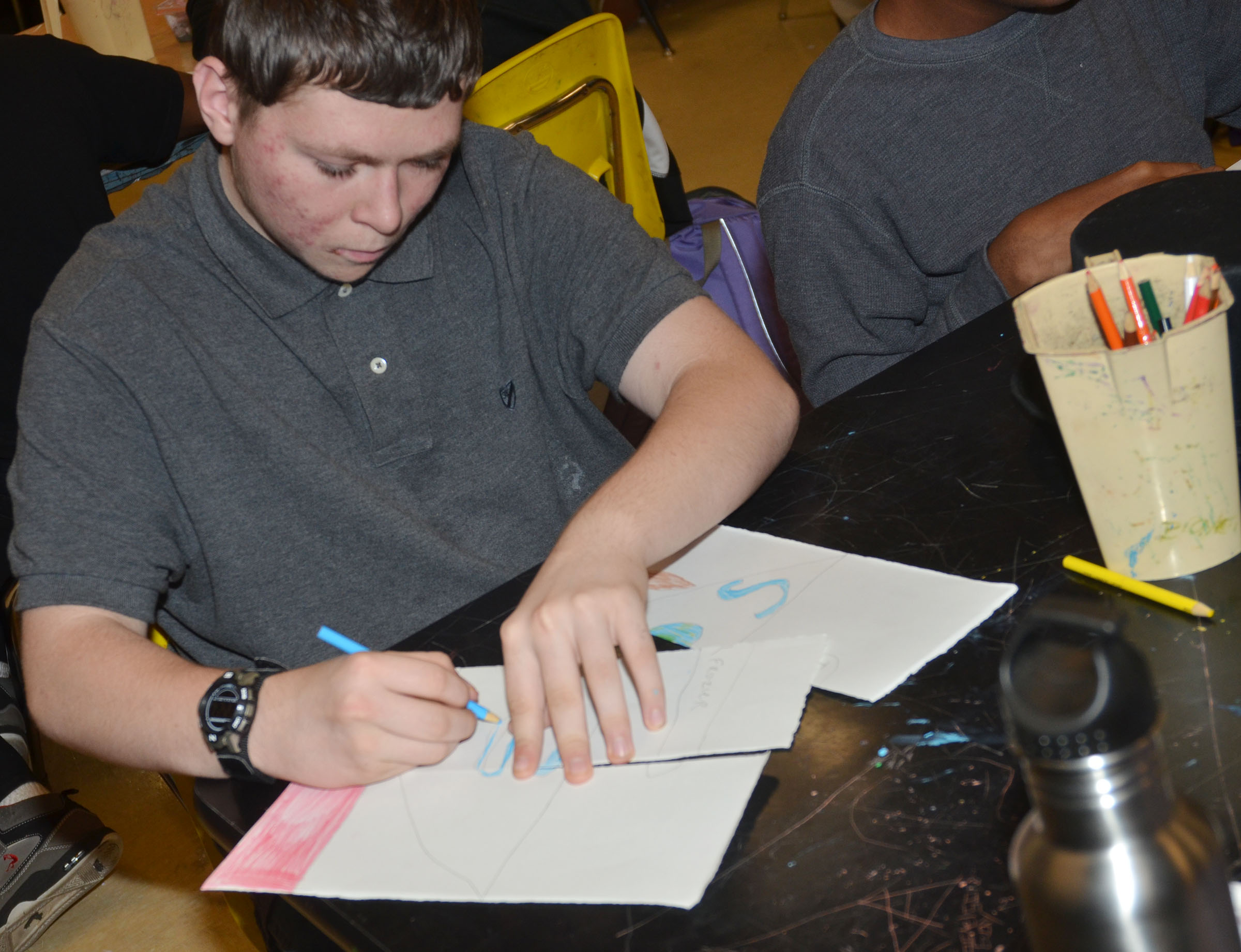 CHS freshman Tyler Frazier draws his design for his triptych panels.