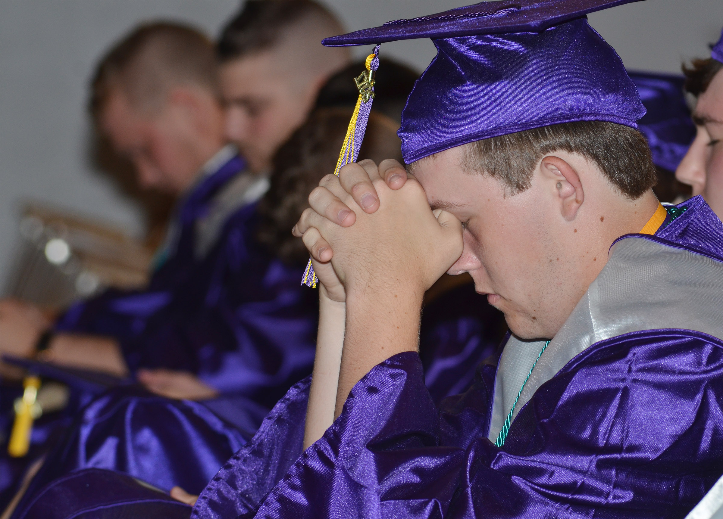 CHS senior Jared Brewster prays during the baccalaureate ceremony.