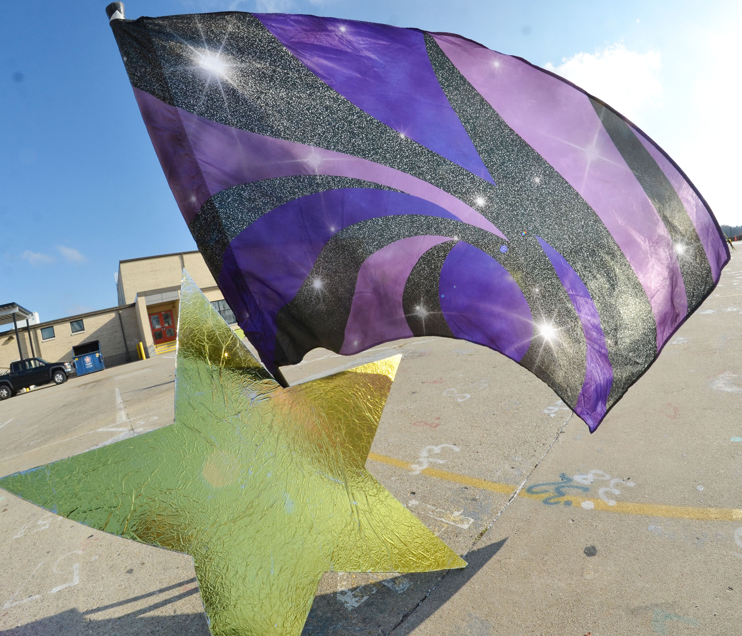 A flag sways in the wind against a CHS Marching Band prop.
