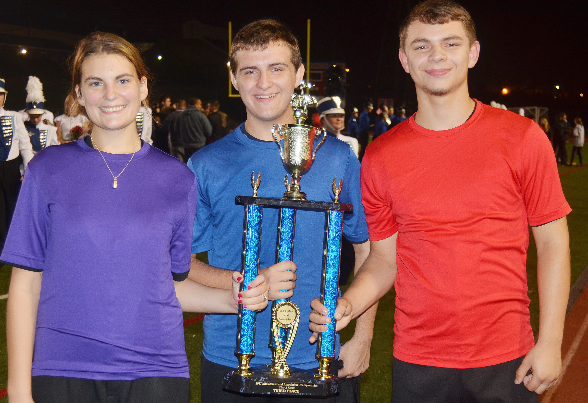 From left, CHS seniors Tiffany Kane, Austin Fitzgerald and Chaz Babbs hold the band's third-place Mid-States Band Association championships trophy.