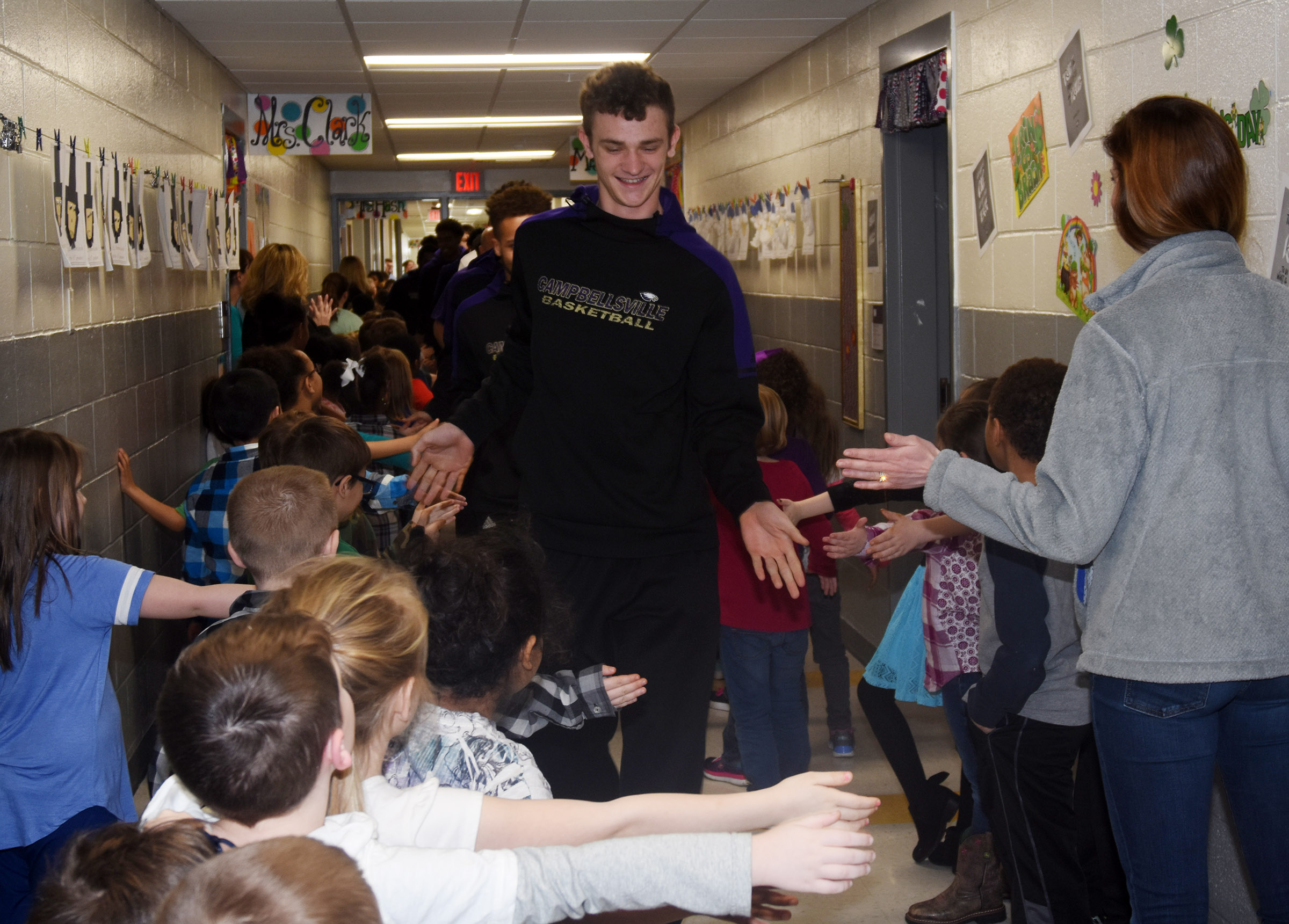 CHS senior Connor Wilson high-fives CES students during the Eagle Walk.