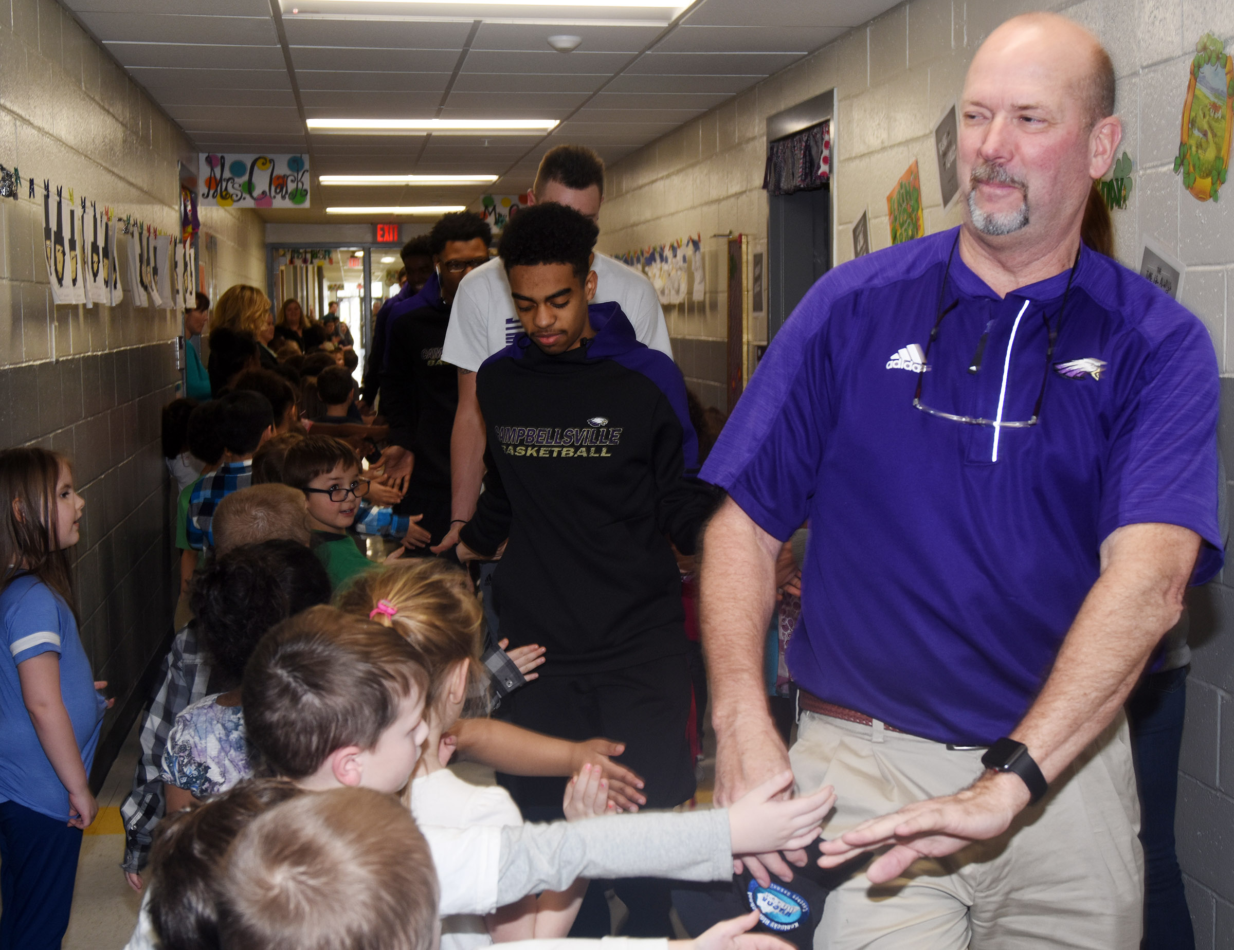 CHS boys' basketball head coach Tim Davis high-fives CES students during the Eagle Walk.