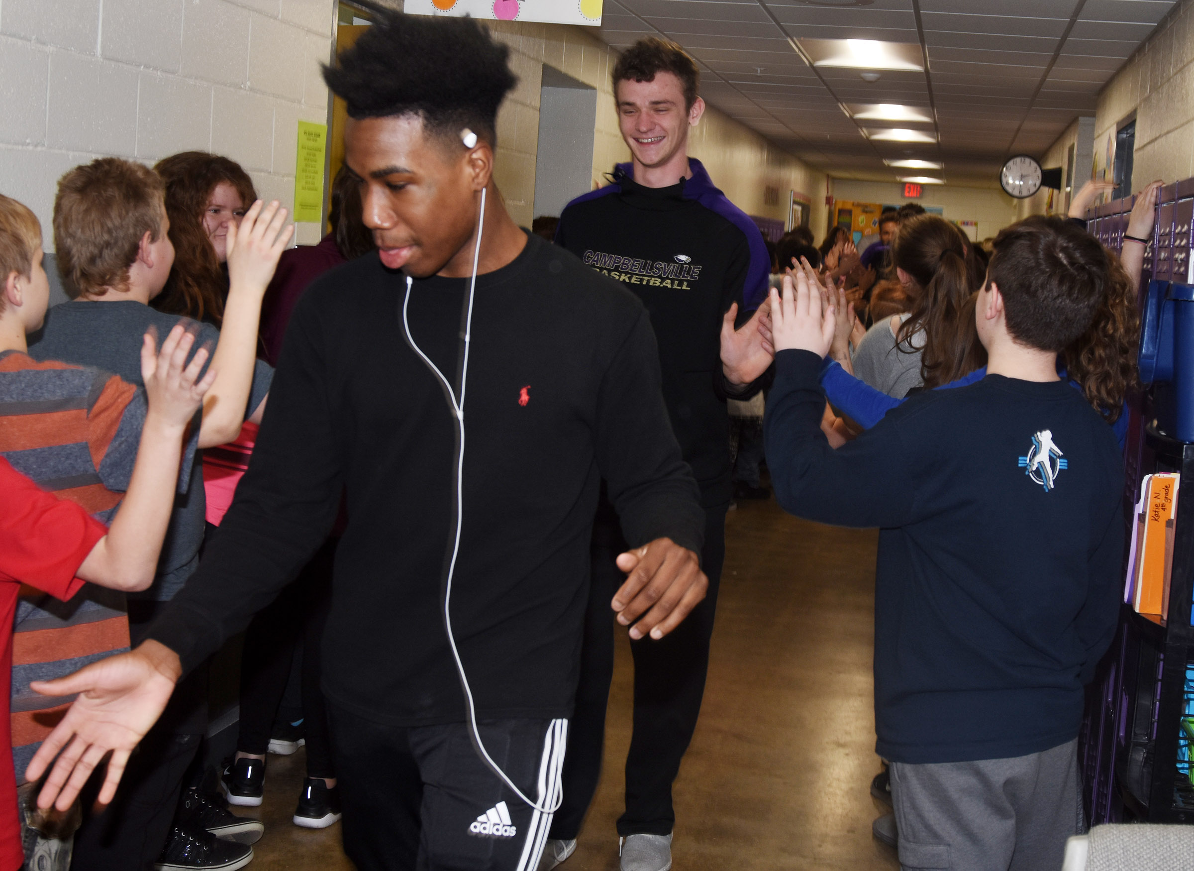 CHS sophomore Malachi Corley, at left, and senior Connor Wilson high-five CES students during the Eagle Walk.