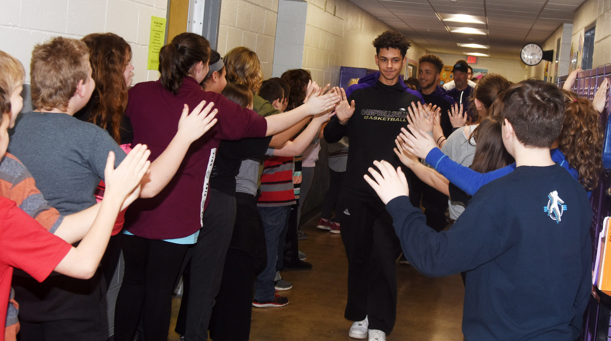 CHS sophomore Mikael Vaught high-fives CES students during the Eagle Walk.