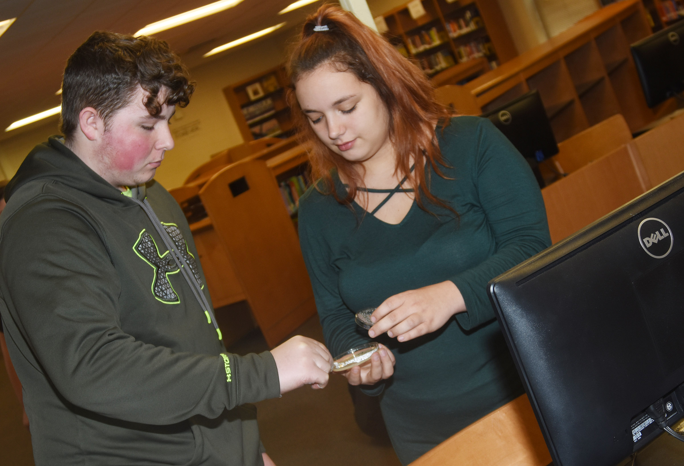 CHS freshman Alex Howard collects bacteria from a computer, as sophomore Autumn Babbs helps him.