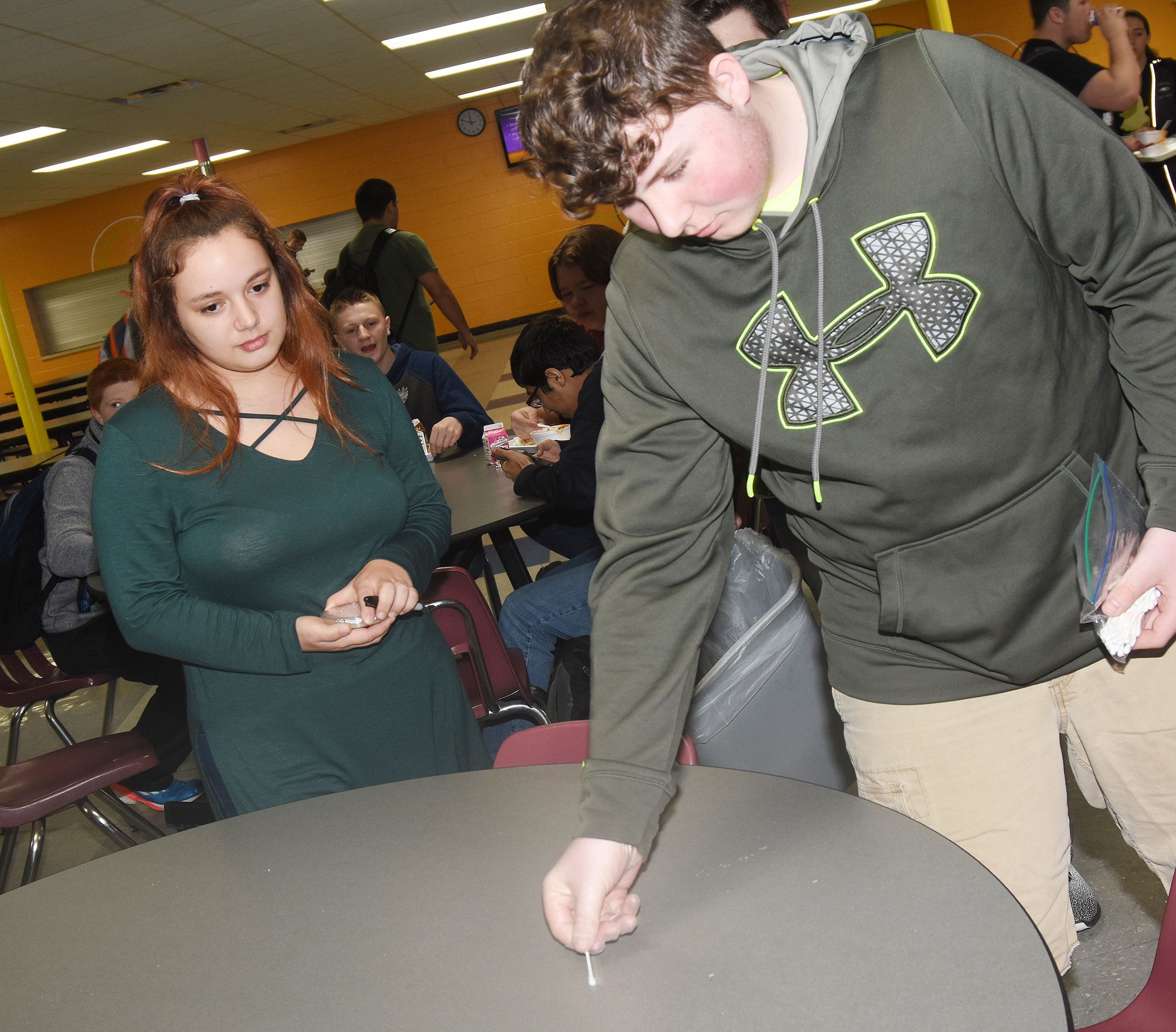CHS freshman Alex Howard collects bacteria from the cafeteria, as sophomore Autumn Babbs helps.