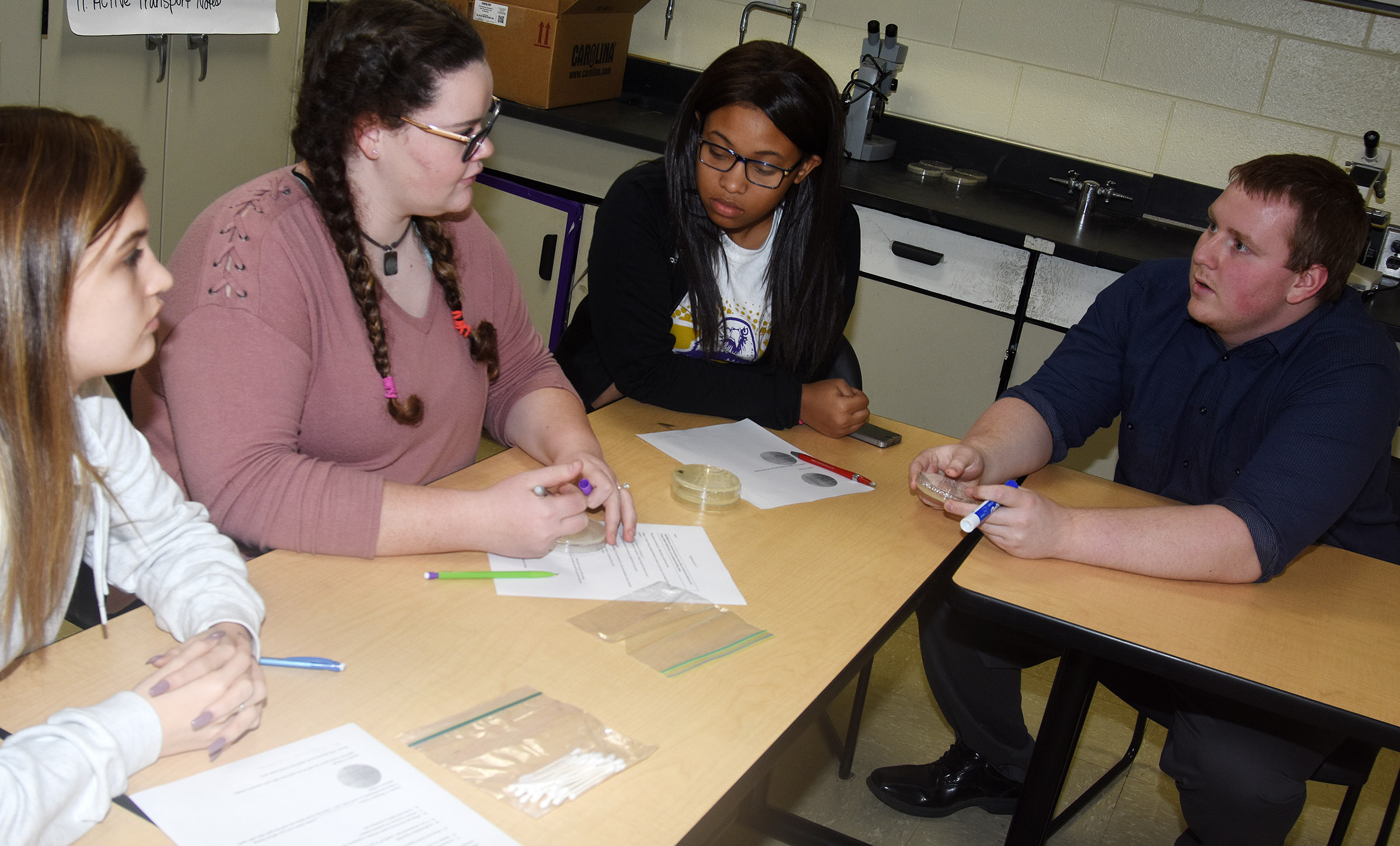 Campbellsville University student teacher T.J. Rahill talks to, from left, freshman Carly Adams and sophomores Shallan Philpott and Ketayah Taylor about how to collect bacteria.